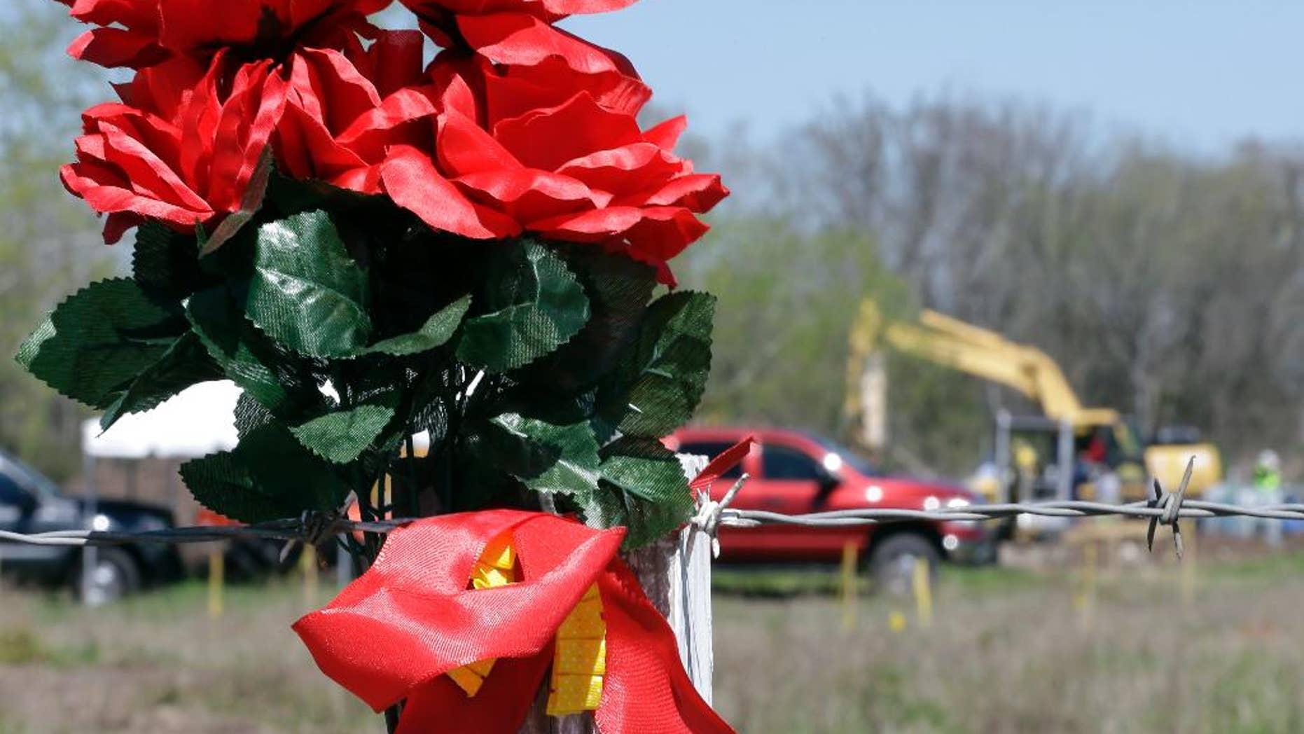 FILE - In this file photo made March 4, 2016, flowers hang on a fence surrounding an area where authorities search for human remains near Houston. A convicted kidnapper has been temporarily released from prison to help authorities who are digging for the body of a teenager who disappeared two decades ago. Denton police say the remains have been identified through dental records as those of Kelli Cox, who went missing from the North Texas town of Denton in July 1997. (AP Photo/David J. Phillip, file)