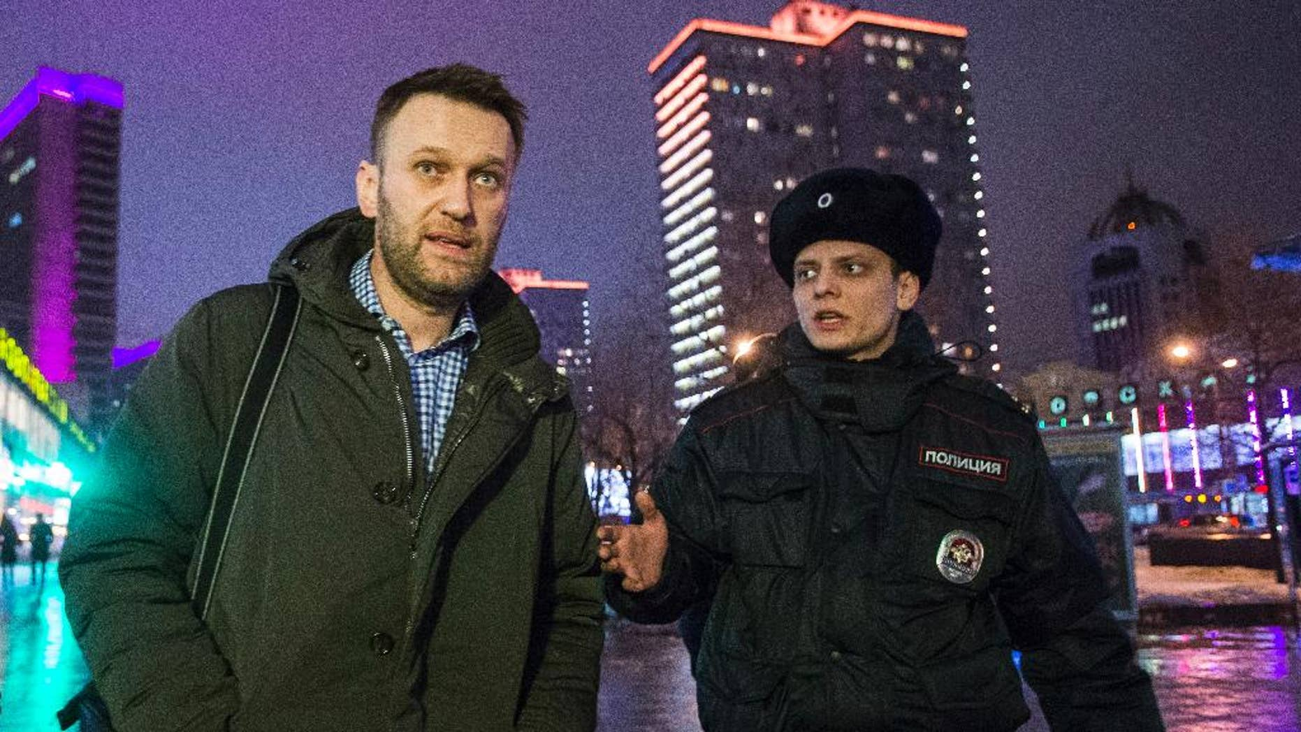Russian opposition activist and anti-corruption crusader Alexei Navalny, left, is detained by police after defying his house arrest to speak on Radio Echo Moskvy in Moscow, Wednesday, Jan. 14, 2015. Leading Russian opposition figure Alexei Navalny says he has paid the state for the electronic bracelet that he cut off to protest his house arrest. Navalny was convicted in late December of fraud and given a suspended sentence. But the court said he must remain under house arrest until his appeals are exhausted. (AP Photo/Pavel Golovkin)
