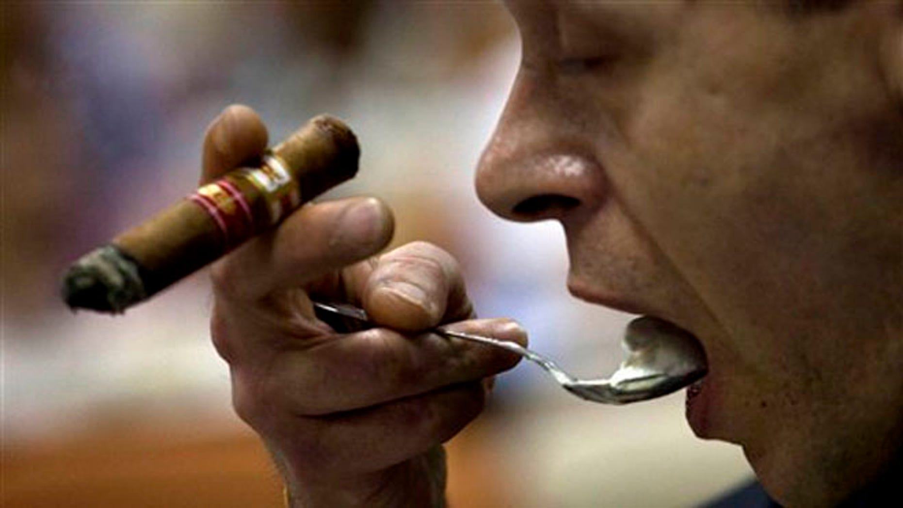 A man eats a dessert as he smokes a cigar during a tobacco cooking event at the 15th Cigar Festival in Havana, Cuba.