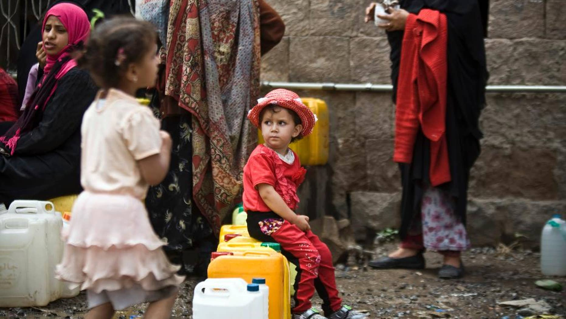 May 9, 2015: A girl waits for her turn to fill buckets with water from a public tap amid an acute shortage of water, in Sanaa, Yemen.