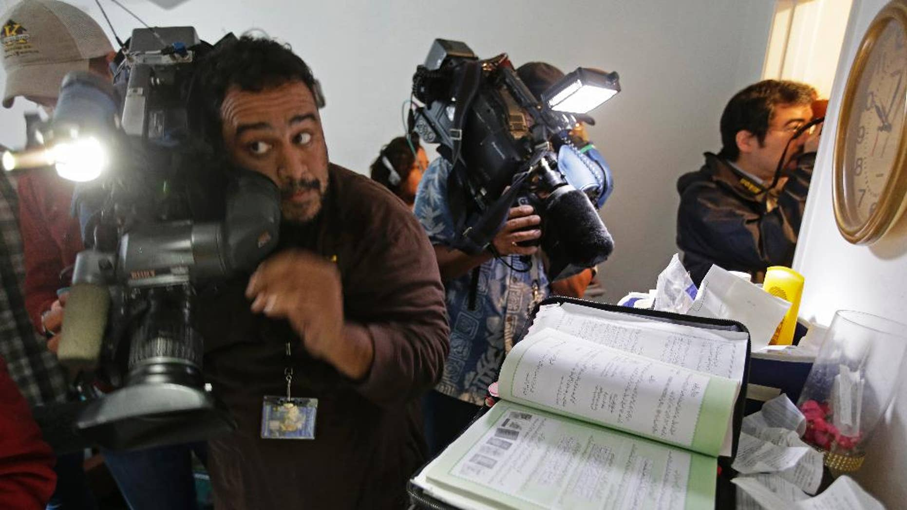 Members of the media crowd into the apartment bedroom of San Bernardino shooting suspects Syed Farook and his wife, Tashfeen Malik, in Redlands, Calif., Friday, Dec. 4, 2015, after the building landlord invited journalists into the townhouse. A book containing passages from the Quran is seen at right.  (AP Photo/Chris Carlson)