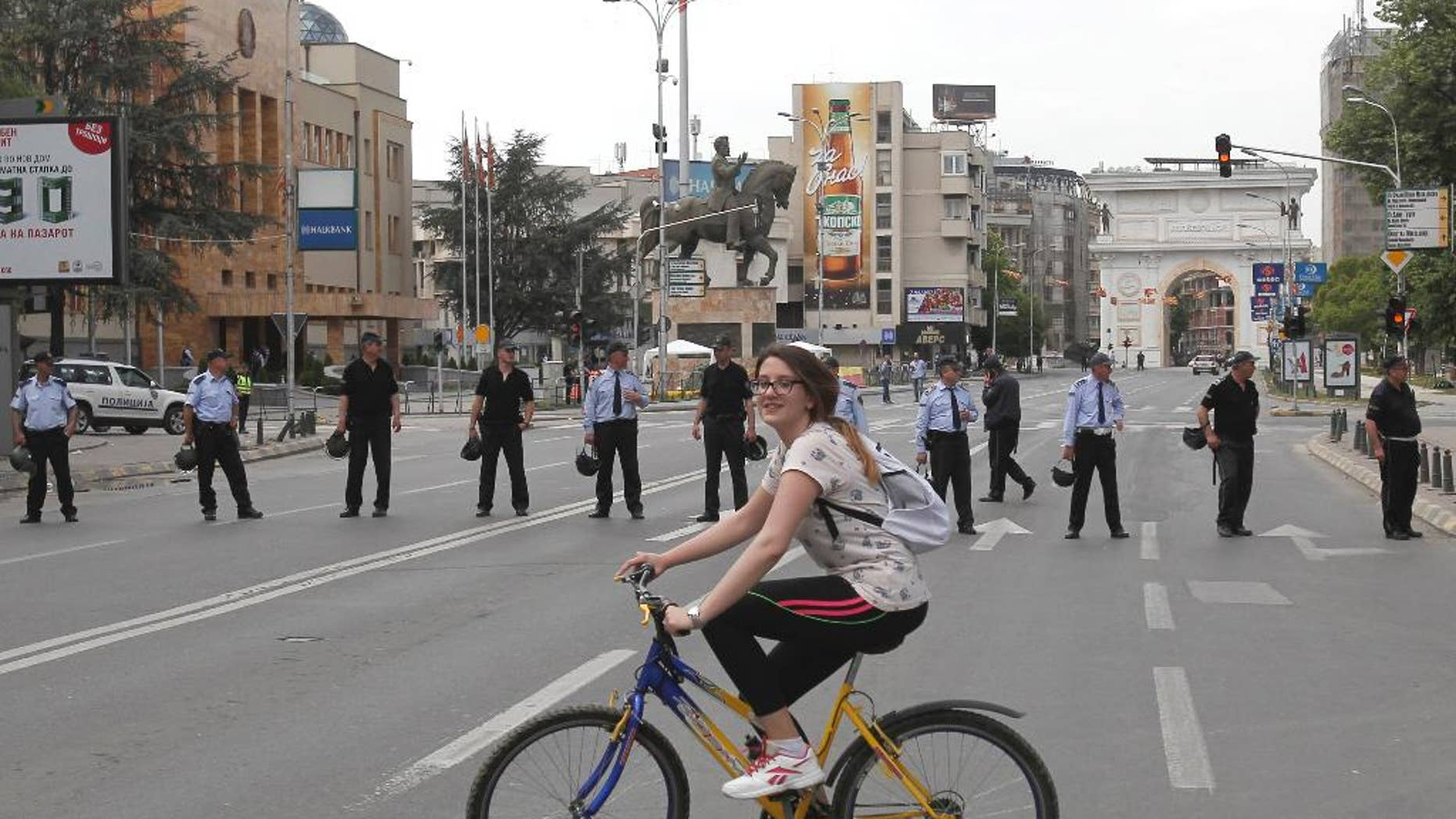 A girl rides a bicycle near a police cordon that blocks the street in front of the parliament building in Skopje, Macedonia, Friday, April 28, 2017.  More than 100 people were injured Thursday evening including protestors, policemen and lawmakers, after protesters broke through a police cordon and entered Macedonian parliament to protest the election of a new speaker, despite a months-long deadlock in talks to form a new government. (AP Photo/Boris Grdanoski)