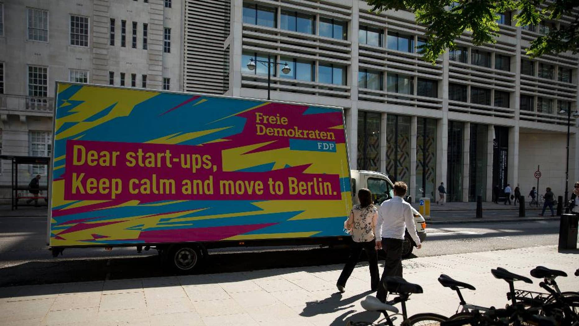 An advert suggesting start-up businesses based in the UK move to Berlin is displayed on a parked vehicle on Finsbury Square in the City of London, Tuesday, July 5, 2016. Its image as a relaxed and relatively affordable city may convince tech companies to relocate to Berlin, which is already home to online retailer Zalando, language-learning service babble and audio sharing platform SoundCloud. Last year, Berlin startups attracted more investment than those in based in London. (AP Photo/Matt Dunham)