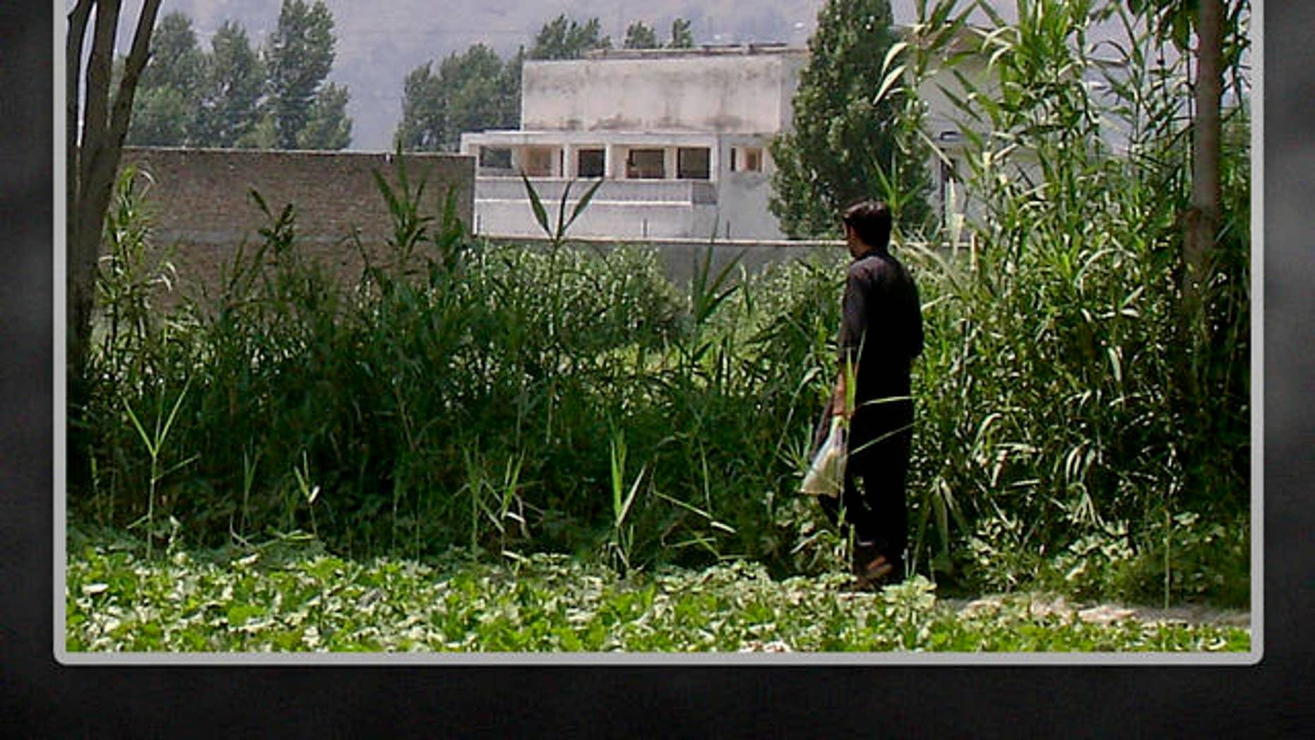 FILE: A local residents walks near a house where Al Qaeda leader Usama bin Laden was killed, Abbottabad, Pakistan.