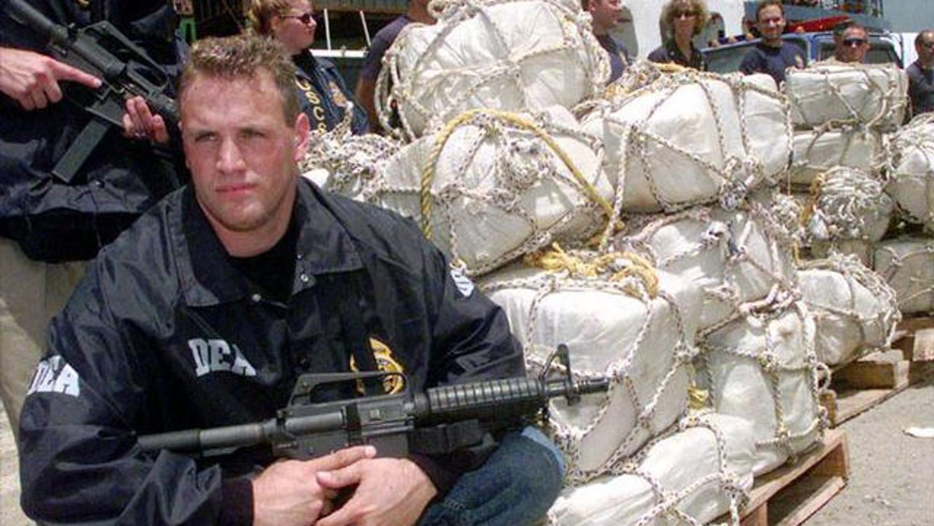 A DEA agent guards a pile of confiscated cocaine (AP Photo)