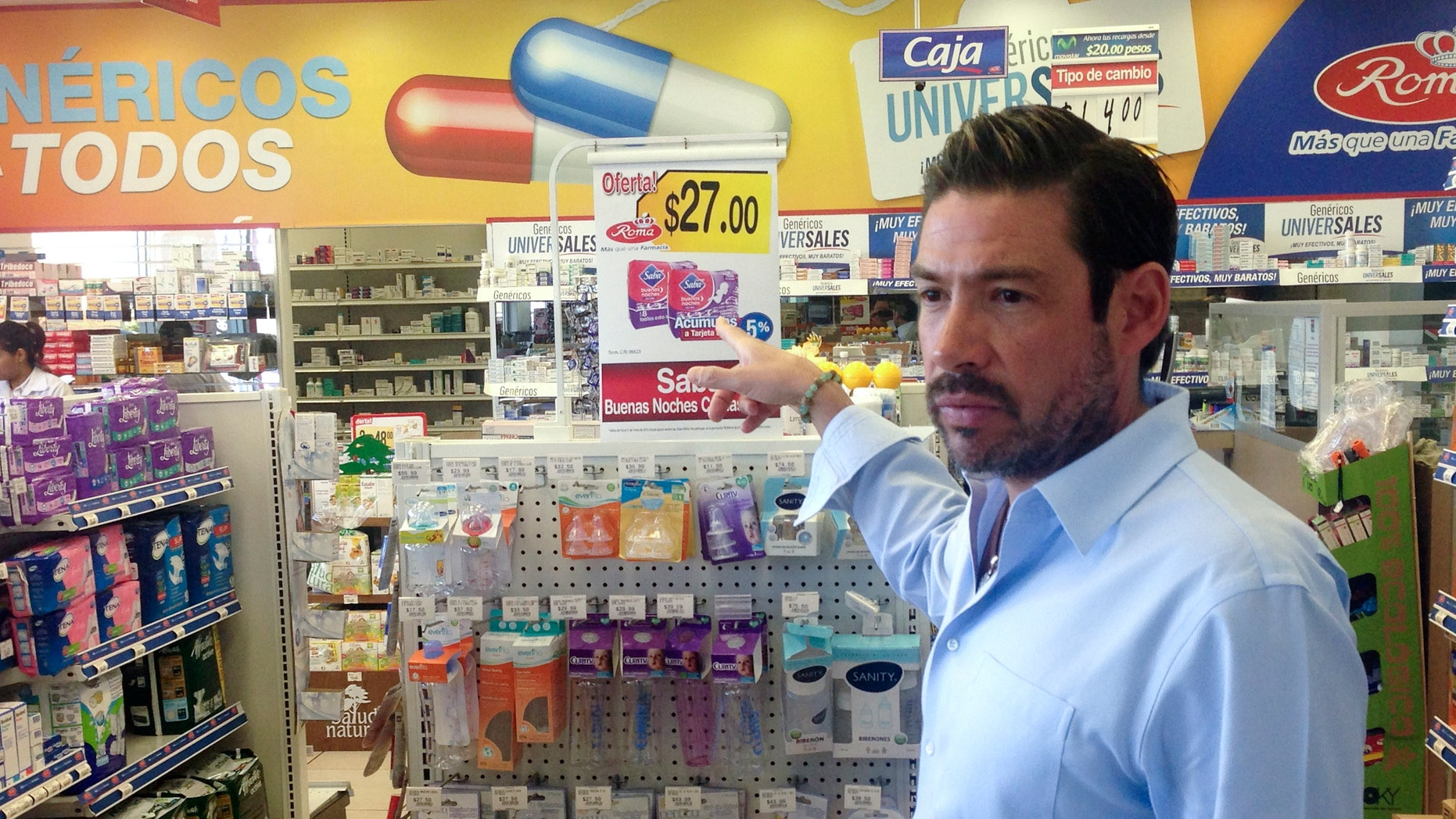 In this Jan. 27, 2015 image, Roberto Castro, chief executive officer of Farmacias Roma, gestures inside one of his locations in Tijuana, Mexico. Castro, who's customers often pay in dollars, faces tough challenges amid a clamor to crack down on money laundering. Many American banks, wary of the potential for massive penalties, have closed Mexican accounts or saddled customers with new restrictions rather than risk the chance. (AP Photo/ Elliot Spagat)