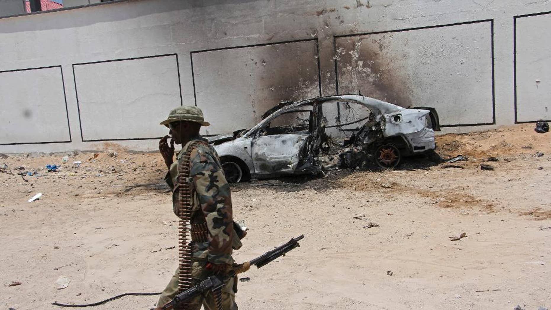 A Somali soldier walks near the wreckage of a car bomb blast near Aden Abdule international airport in Mogadishu, Somalia, Sunday, April, 16, 2017. A Somali police officer says a car bomb detonated near the Somali capital's airport. (AP Photo/Farah Abdi Warsameh)