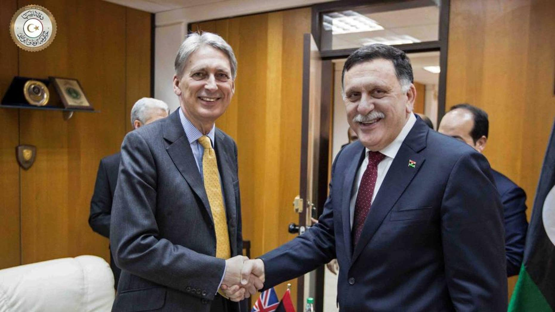 In this photo provided by the Libyan Government of National Accord, Libyan prime minister-designate Fayez Serraj , right and British Foreign Secretary Philip Hammond shake hands for photographers in Tripoli, Libya, Monday, April 18, 2016. Western nations hope the U.N.-backed government, known as the Government of National Accord or the GNA, can unite the country in order to combat an increasingly powerful Islamic State affiliate. (Libyan Government of National Accord via AP)