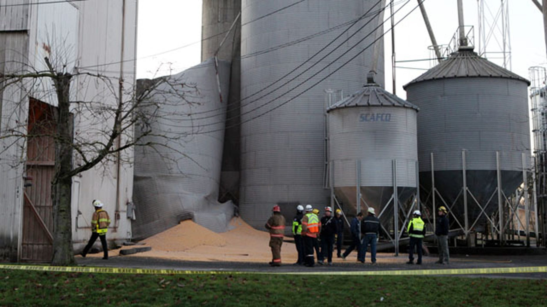 December 2, 2013: Emergency responders from the South Pierce Fire Department respond to a grain processing feed mill owned by Wilcox Farms in downtown Roy, Wash., after one of its silos collapsed. (AP Photo/The Olympian)