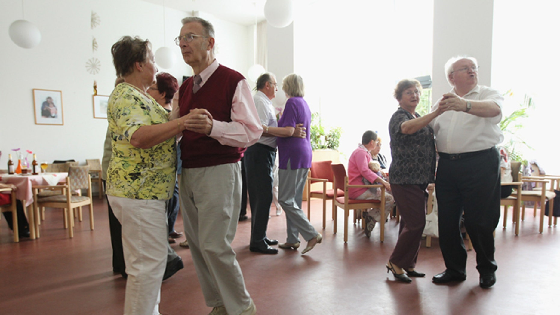 Elderly people dance during an afternoon get-together in the community room of the Sewanstrasse senior care home in Lichtenberg district on August 30, 2011 in Berlin, Germany.