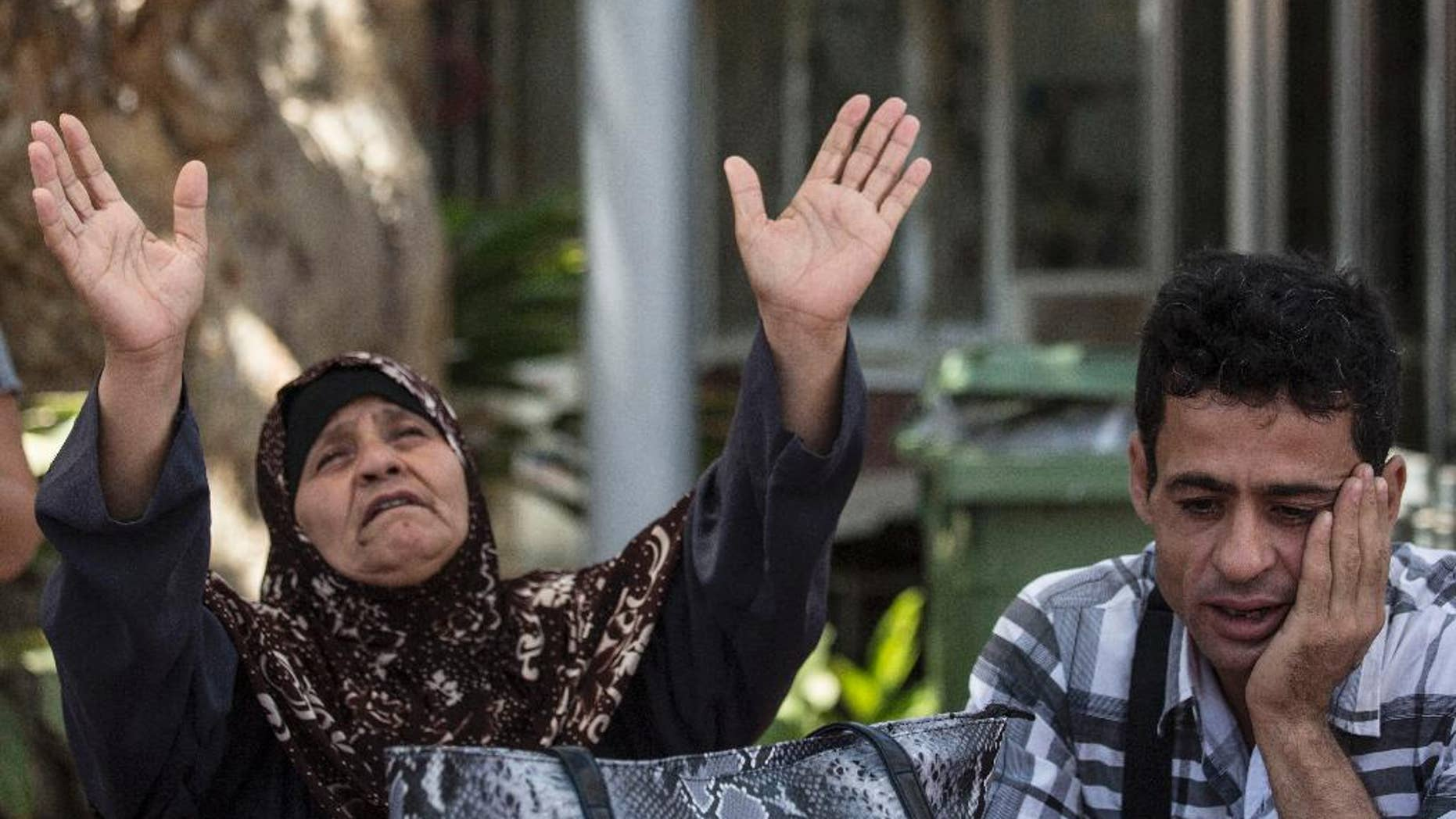 Mazoza Allan , left, and Amid Allan, a brother of Mohammed Allan, a Palestinian prisoner on a hunger strike, wait outside Barzilai hospital in Ashkelon, southern, Israel, Wednesday, August 19, 2015. Israel's Supreme Court is hearing a petition to immediately release Allan who has been on a hunger strike for 65 days. Allan's lawyer says the state has proposed a compromise under which Allan would be released in November, if he agrees to end his hunger strike. (AP Photo/Tsafrir Abayov)