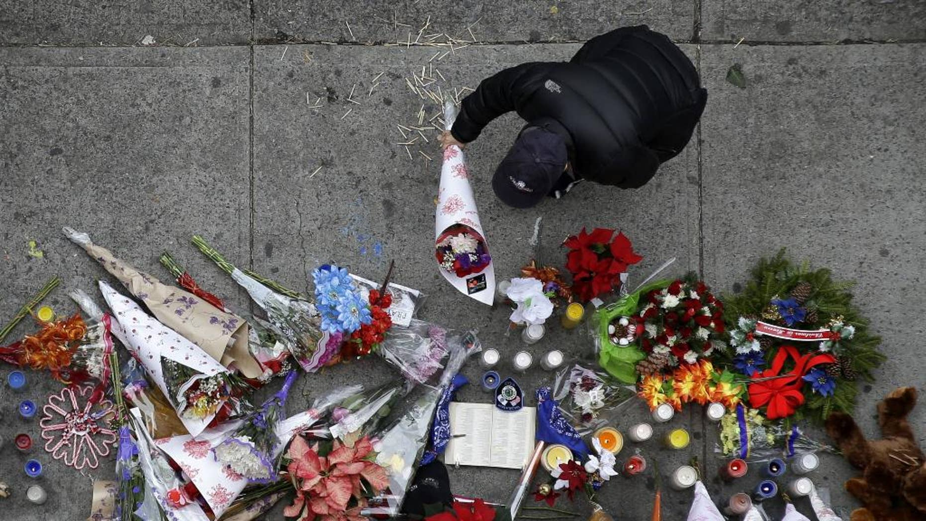 A man leaves flowers at an impromptu memorial near the site where two police officers were killed the day before in the Brooklyn borough of New York, Sunday, Dec. 21, 2014. Police say Ismaaiyl Brinsley ambushed officers Rafael Ramos and Wenjian Liu in their patrol car in broad daylight Saturday, fatally shooting them before killing himself inside a subway station. (AP Photo/Seth Wenig)