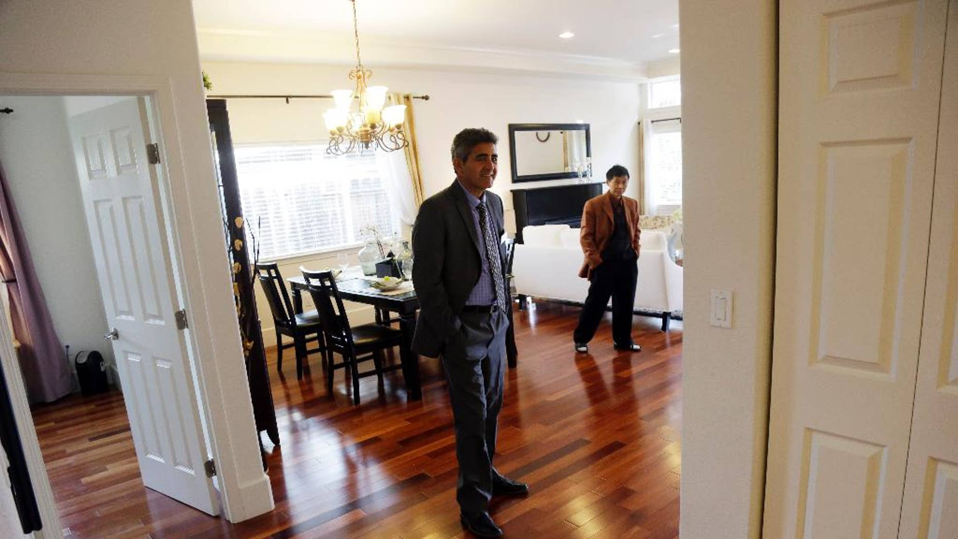 In this Jan. 8, 2015 photo, real estate agent Sam Golkar, left, tours a home being sold by fellow agent Frank Ruan, right, in Cupertino, Calif. The National Association of Realtors reports on sales of existing homes in December on Friday, Jan. 23, 2015. (AP Photo/Marcio Jose Sanchez)