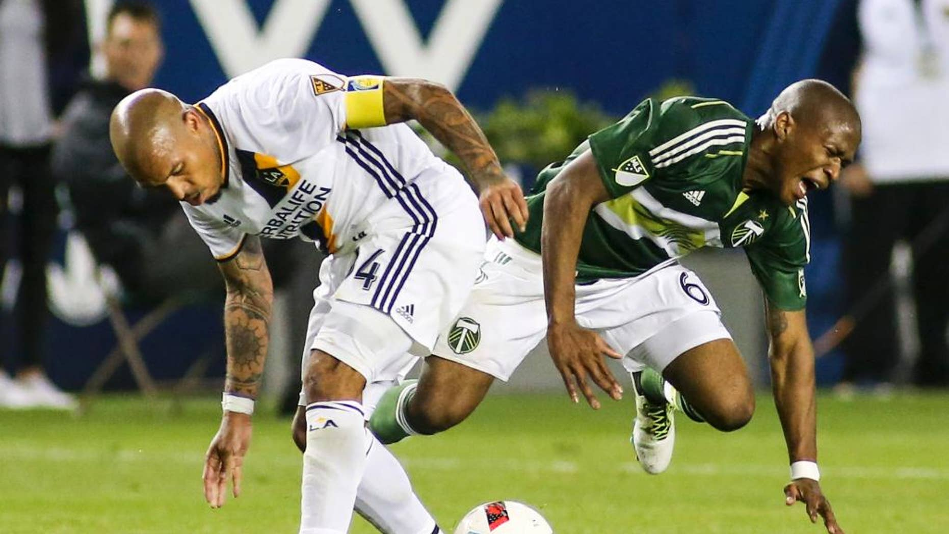Los Angeles Galaxy midfielder Nigel de Jong, left, crashes into Portland Timbers midfielder Darlington Nagbe during the second half of an MLS soccer game in Carson, Calif., Sunday April 10, 2016. The game ended in a 1-1 draw. (AP Photo/Ringo H.W. Chiu)