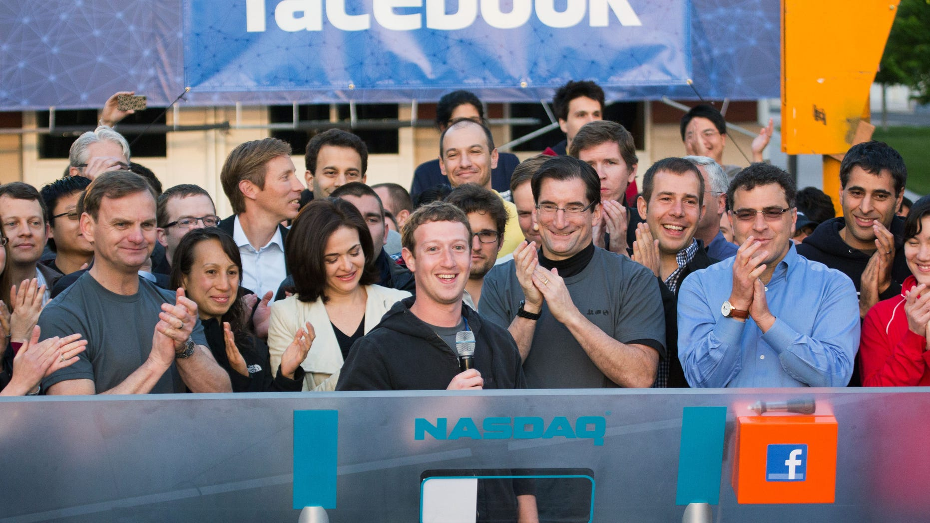Chairman and CEO Mark Zuckerberg, center, rings the opening bell of the Nasdaq stock market.