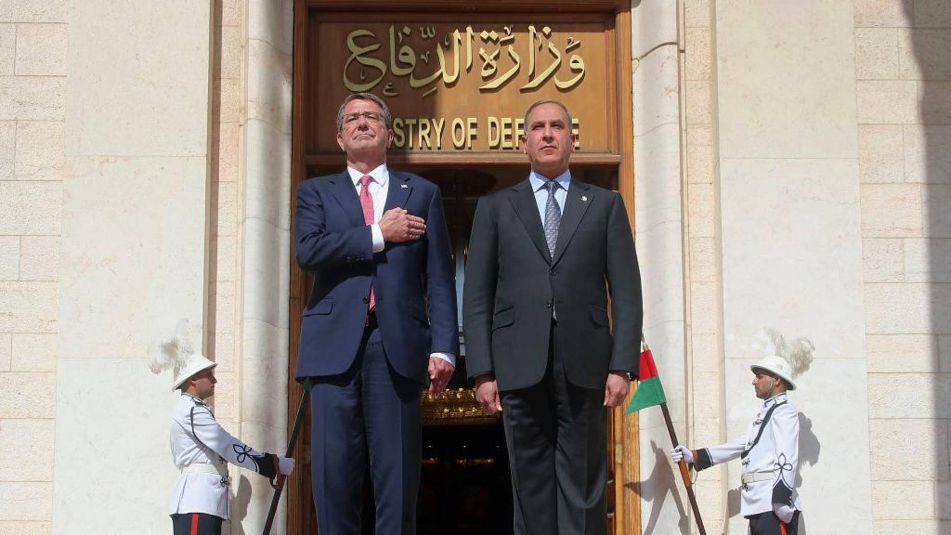 FILE - In this Monday, April 18, 2016 file photo, visiting U.S. Defense Secretary Ash Carter, left, and his Iraqi counterpart, Khaled al-Obeidi, stand for their country's national anthems during a welcome ceremony at the Ministry of Defense in Baghdad, Iraq. On Saturday, Dec. 3, 2016, Carter said the American military, along with its international partners, will need to remain in Iraq even after the expected defeat of the Islamic State group. (AP Photo)