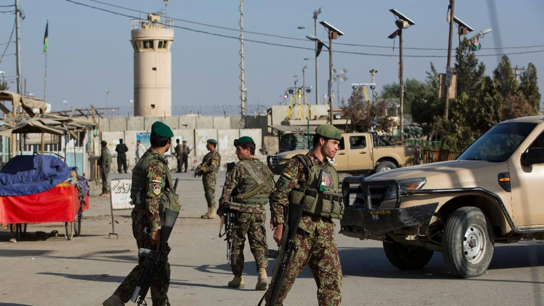 Afghanistan's National Army soldiers guard, blocking the main road to the Bagram Airfield's main gate in Bagram, north of Kabul, Afghanistan, Saturday, Nov. 12, 2016. An explosion at a U.S. airfield in Afghanistan early Saturday killed four people, the head of international forces in the country said. (AP Photos/Massoud Hossaini)
