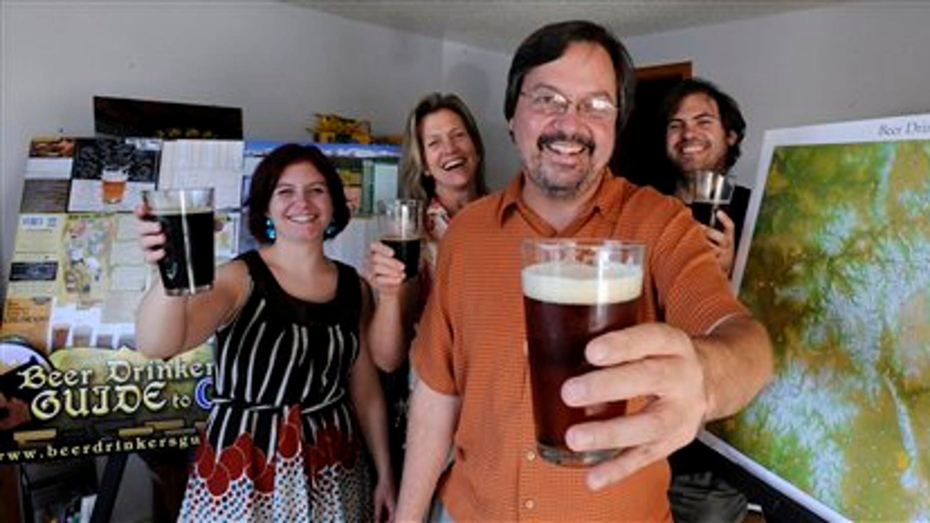 Aug. 8:  Mike Laur, foreground, raises a beer along with, left to right, Zenia Brink, Carol White and Rick Mazzola, who helped him create the fourth edition of the Beer Drinker's Guide to Colorado map in Colorado Springs, Col.  The latest edition of the guide, put together by Laur and his 3.5 employees (one works part time), lists 126 breweries, 20 more than when he launched the publication in 2008.