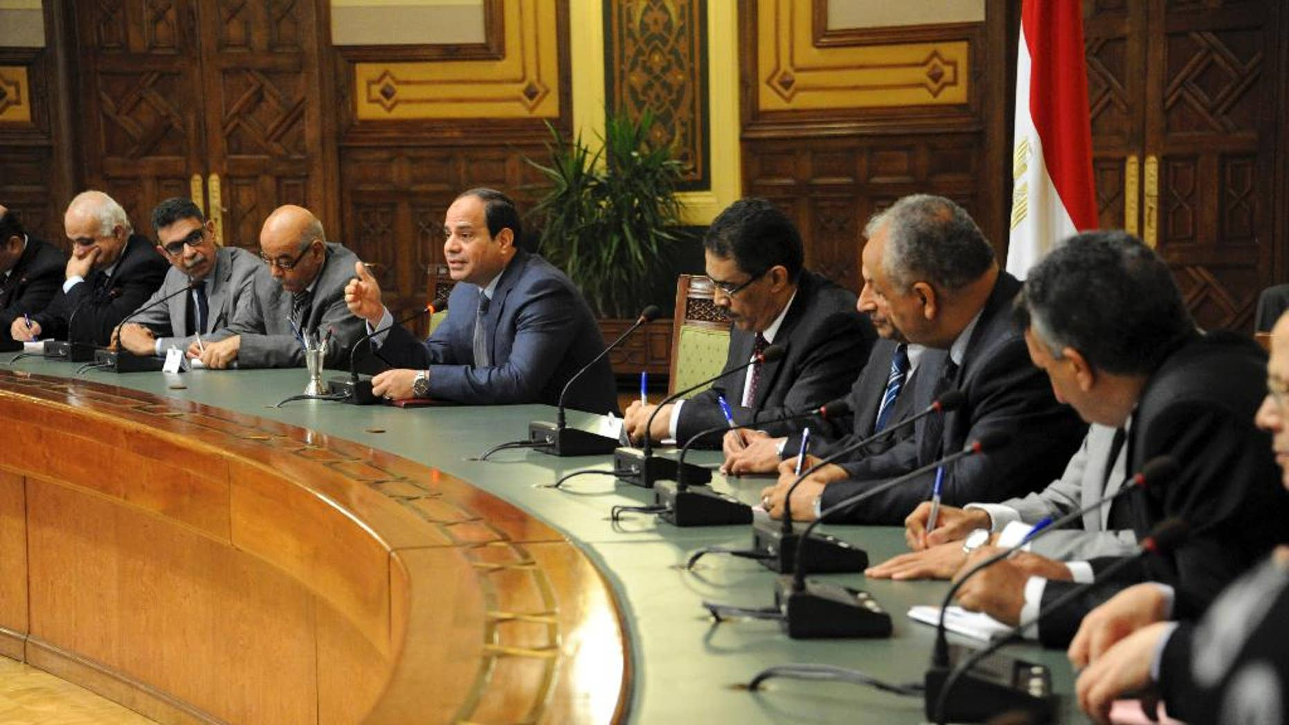 In this photo provided by Egypt's state news agency MENA, Egyptian President Abdel-Fattah el-Sissi, center, meets with editors of Egyptian newspapers and media in the presidential palace, in Cairo Egypt, Sunday, Aug. 24, 2014. El-Sissi denied Sunday any military involvement in neighboring Libya, a day after Islamist militias accused Cairo of bombing their posts in Tripoli, Egypt's state news agency reported. El-Sissi said Egypt is in consultation with Libya's neighbors to find a political solution to the violent power struggle between rival groups. (AP Photo/MENA)