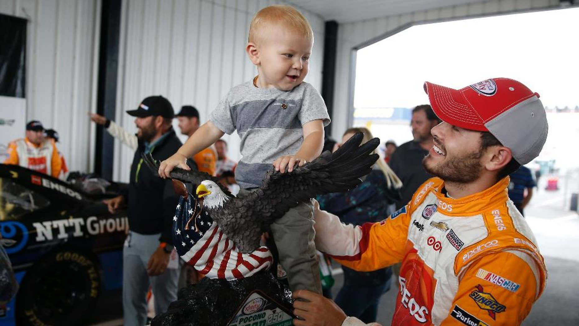 Kyle Larson, right, plays with his son Owen Larson and the trophy after he won the rain-shortened NASCAR Xfinity series auto race at Pocono Raceway, Saturday, June 4, 2016, in Long Pond, Pa. Larson led when the rain hit 53 laps into the scheduled 100-lap race and the race was called 1 hour, 35 minutes after the red flag came out. (AP Photo/Matt Slocum)