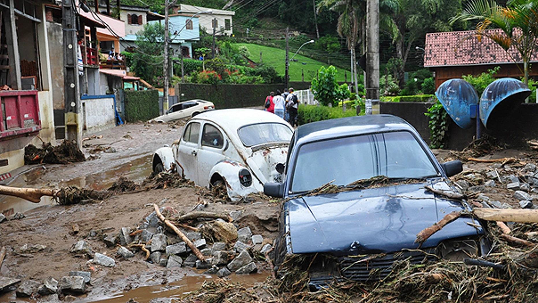 Jan. 12: Cars sit in debris in a flooded street in Teresopolis, Rio de Janeiro state, Brazil.