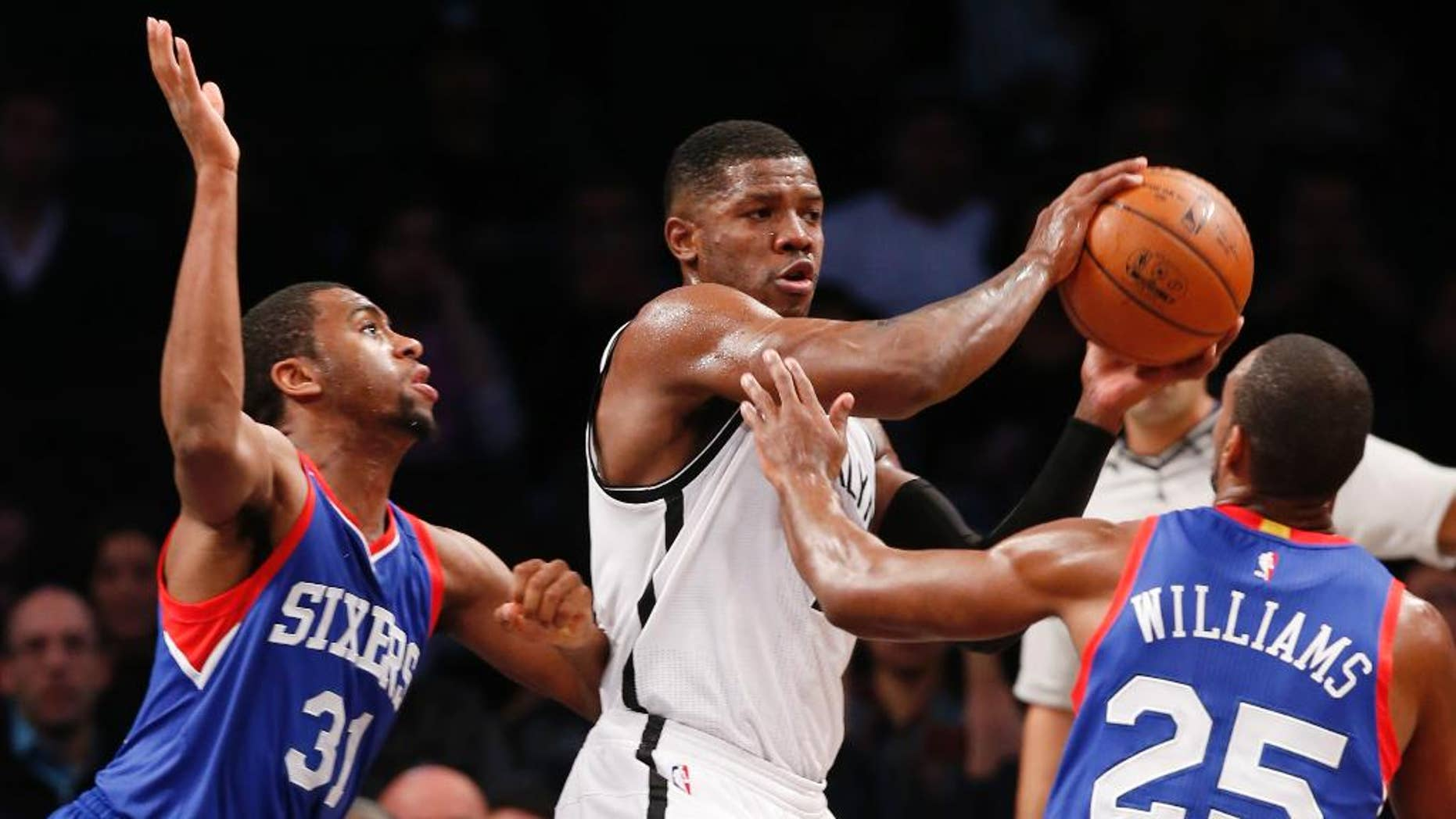 Brooklyn Nets guard Joe Johnson (7) looks to pass as Philadelphia 76ers guard Hollis Thompson (31) and 76ers guard Elliot Williams (25) defend in the first half of an NBA basketball game at the Barclays Center, Monday, Oct. 20, 2014, in New York. (AP Photo/Kathy Willens)