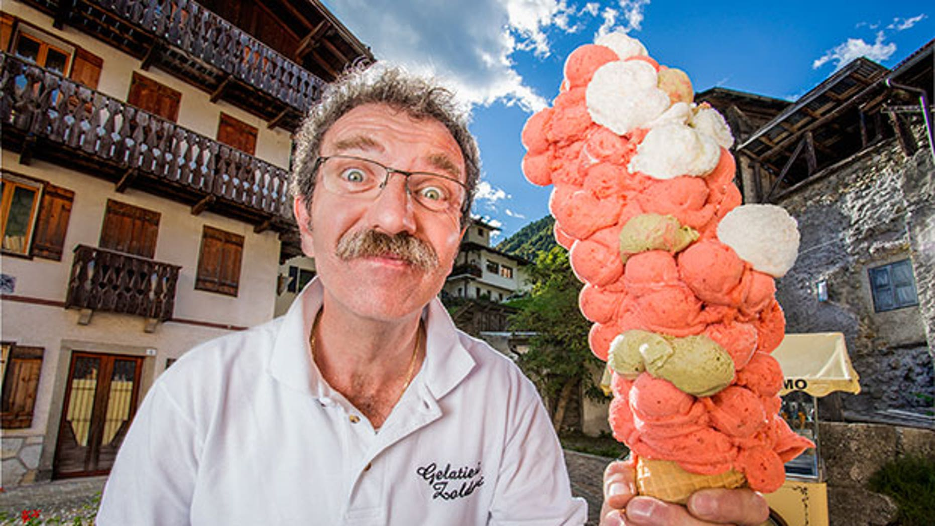 Italian Dimitri Panciera balances his record-breaking gelato cone with 121 individual scoops of ice cream.