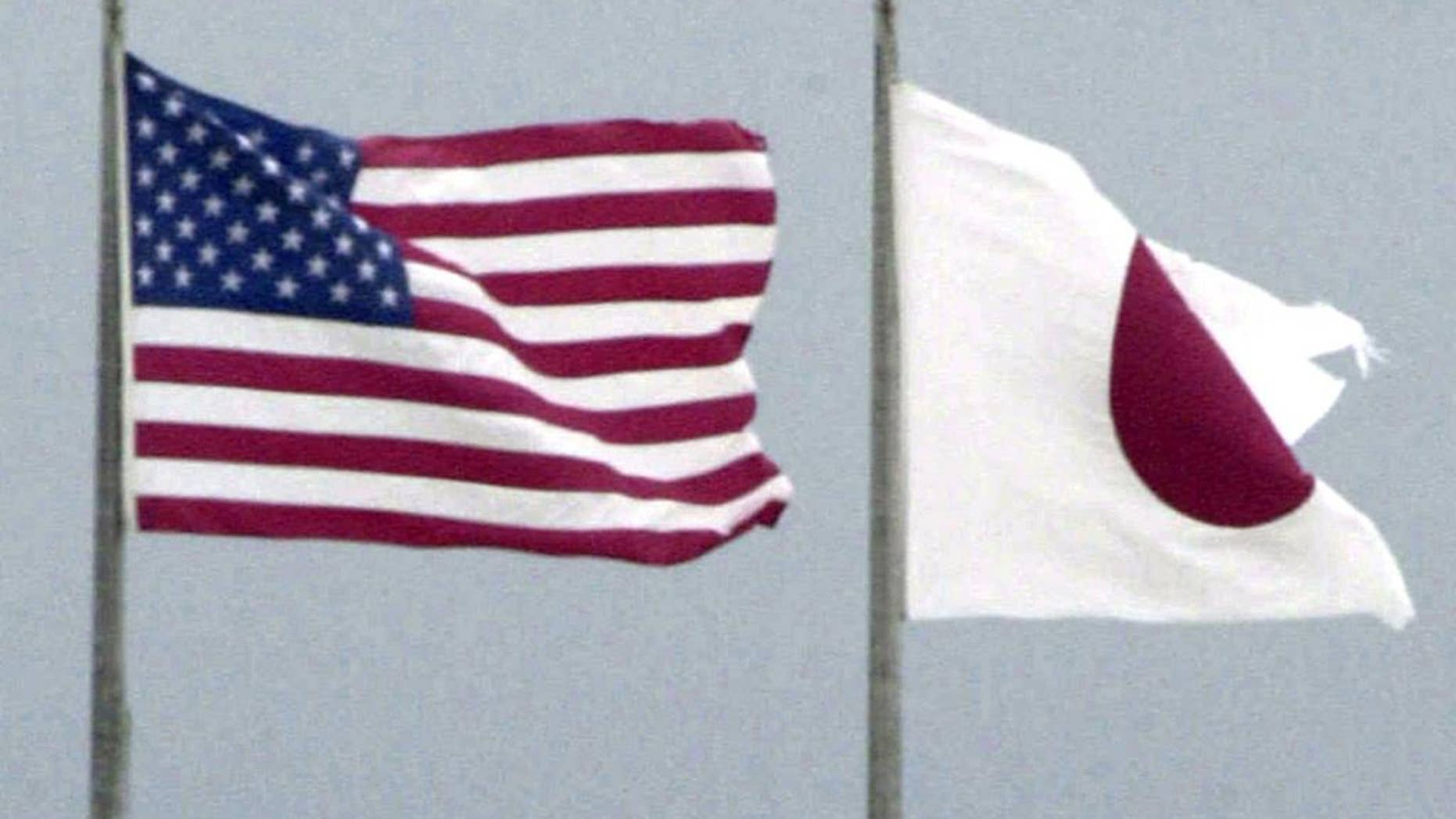 In this Sept. 23, 2001 photo,   flags of U.S. and Japan flutter in U.S. Kadena Air Base on the southern island of Okinawa in Japan.   An American sailor has tapped a cloud-based technology for mobile phones to make it easier to have volunteers take turns driving drunk friends home, an initiative that has curtailed drunken driving among the Navy ranks. The effort, tested at the Naval Sea Systems Command in Charleston, South Carolina, from February, 2016 could also help ease tensions on the southwestern Japanese island of Okinawa, where most of the U.S. troops in Japan are assigned. (Kyodo News via AP) JAPAN OUT, CREDIT MANDATORY