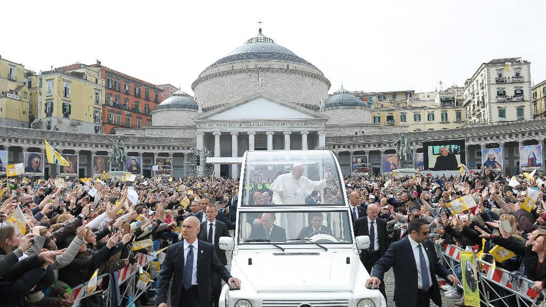 In this March 21, 2015 pool photo, made available Monday, March 23, 2015, Pope Francis, center, is cheered by faithful as he arrives with his popemobile to celebrate a Mass, in Naples, Italy. Pope Francis made an impassioned defense of the unemployed during a speech to people in the poor Neapolitan neighborhood of Scampia Saturday. (AP Photo/L'Osservatore Romano, Pool)