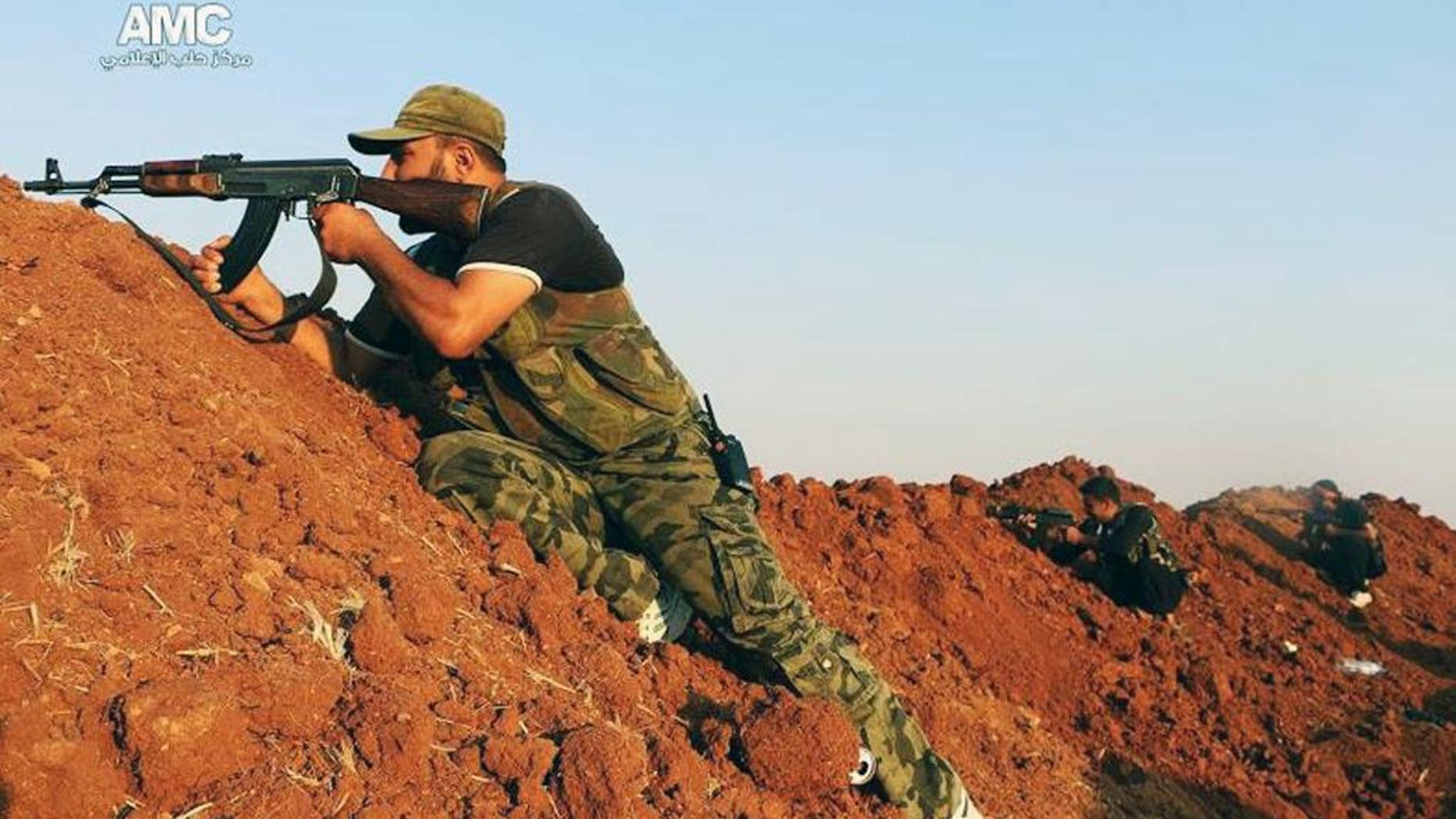 Sunday, Aug. 17, 2014: This photo provided by the anti-government activist group Aleppo Media Center (AMC), which has been authenticated based on its contents and other AP reporting, shows a Free Syrian Army fighter aiming his weapon during a battle with Islamic State militants in Aleppo, Syria.