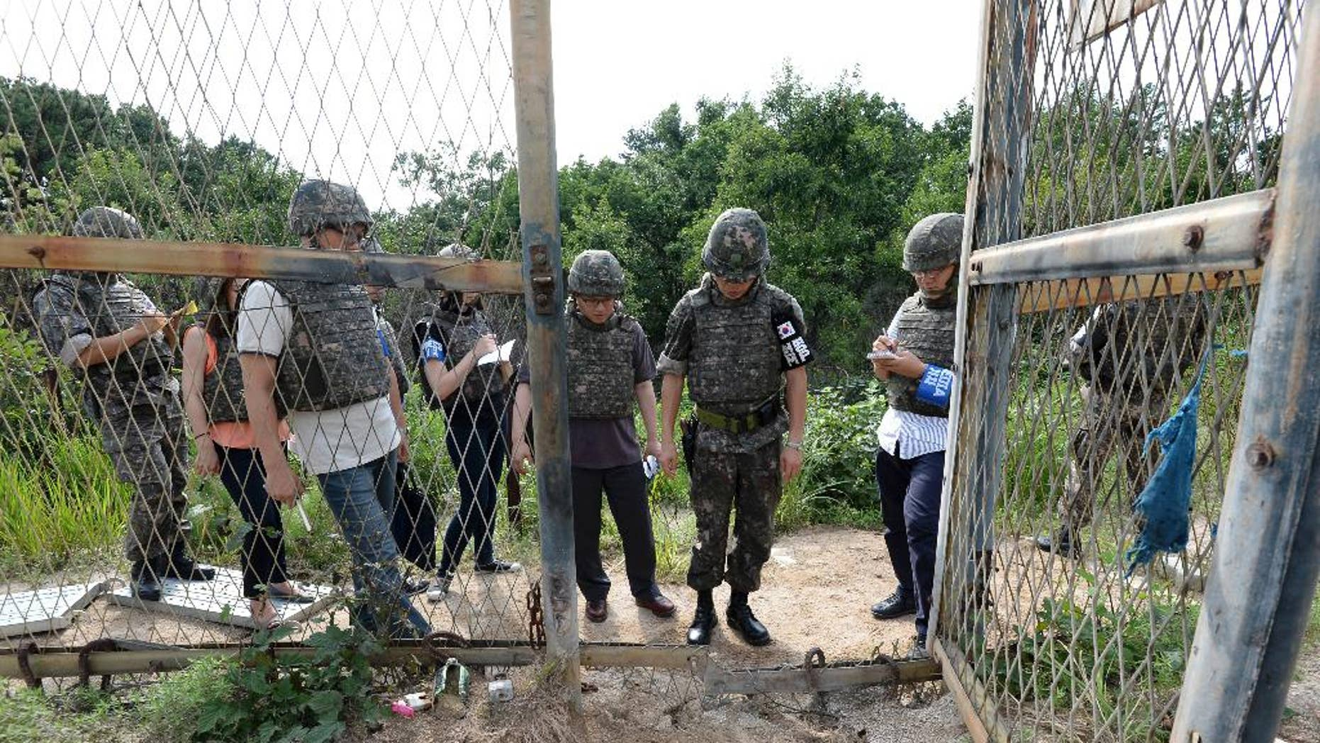 """FILE - In this Aug. 9, 2015 file photo provided by the Defense Ministry, an unidentified South Korean army official, second from right, gives a briefing to the media at the scene of a blast inside the demilitarized zone in Paju, South Korea. North Korea insisted Tuesday, Sept. 1, 2015 that its recent expression of """"regret"""" over a mine explosion that maimed two South Korean soldiers was not an apology, as Seoul claims it was. (The Defense Ministry via AP, FIle)"""
