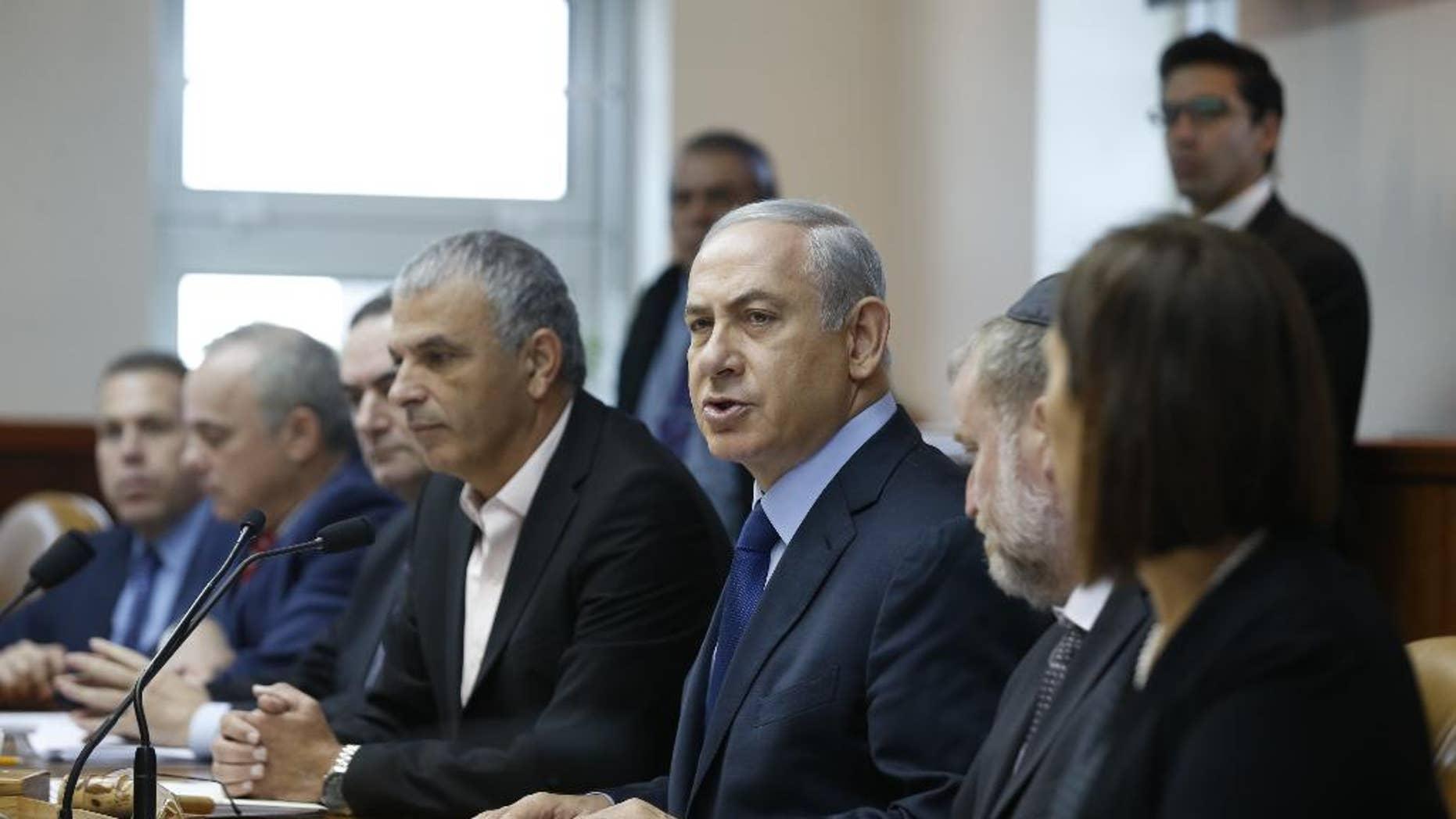 Israel's Prime Minister Benjamin Netanyahu, center, speaks during the weekly cabinet meeting in Jerusalem, Sunday, Dec. 13, 2015. (Baz Ratner/Pool Photo via AP)