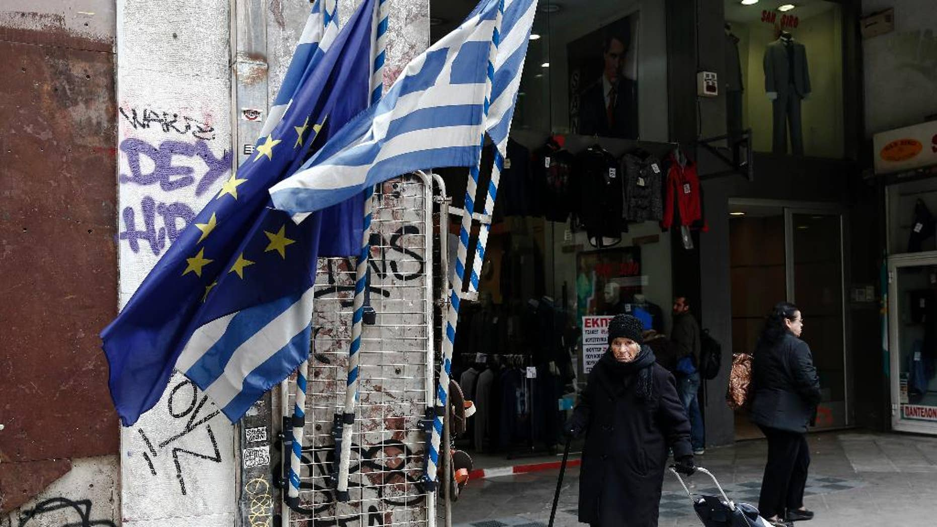 A woman pulls a shopping trolley next to a Greek and an EU flags at a main street of Athens, Thursday, Jan. 26, 2017. Greece's prime minister on Wednesday marked two years in office, as talks with bailout lenders remain at an impasse. (AP Photo/Yorgos Karahalis)