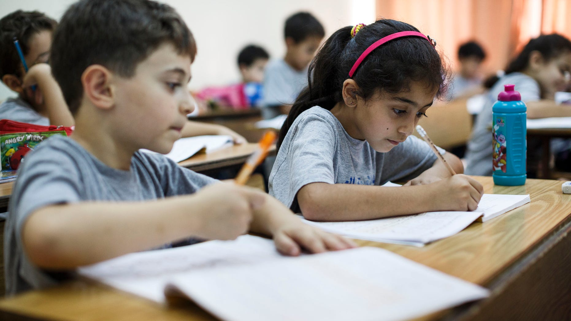 RAMALLAH, WEST BANK - SEPTEMBER 17:  Palestinian children take notes in their notebooks during a math class on September 17, 2013 in Ramallah, West Bank.   The West Bank is a landlocked territory which has an estimated population of  2, 622,544 with Arabs making up almost 80% of the population. It is a disputed territory after Israel captured the land during the six day war in 1967. (Photo by Ilia Yefimovich/Getty Images)