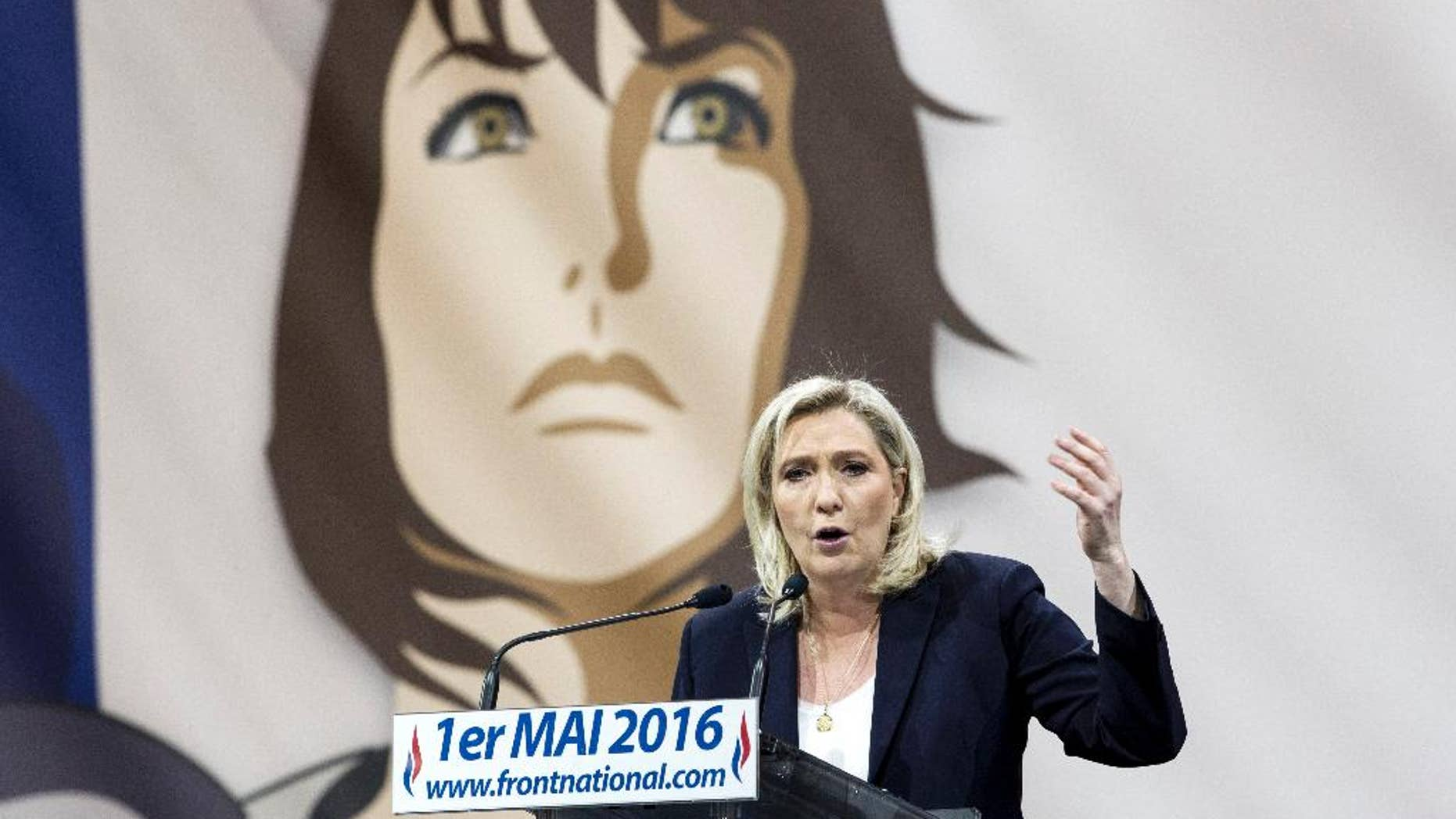 France's far-right National Front party leader Marine Le Pen addresses her supporters as part of a May Day party lunch in Paris, France, Sunday, May 1st, 2016. On background is a portrait of Joan of Arc — the party's patron saint . Jean-Marie Le Pen, a founder and the decades-long leader of France's far-right National Front, declared Sunday that his daughter, Marine Le Pen, the party president who has expelled him, will lose next year's presidential race if she fails to unify the party. (AP Photo/Kamil Zihnioglu)