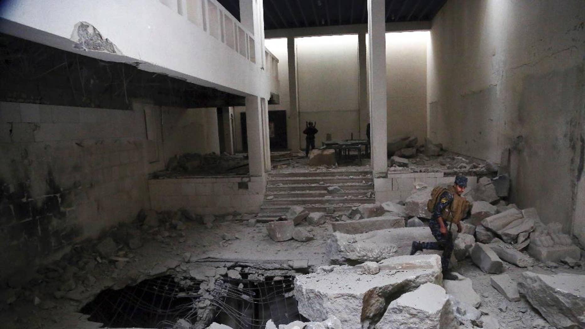 Iraqi police inspect Mosul's damaged museum.