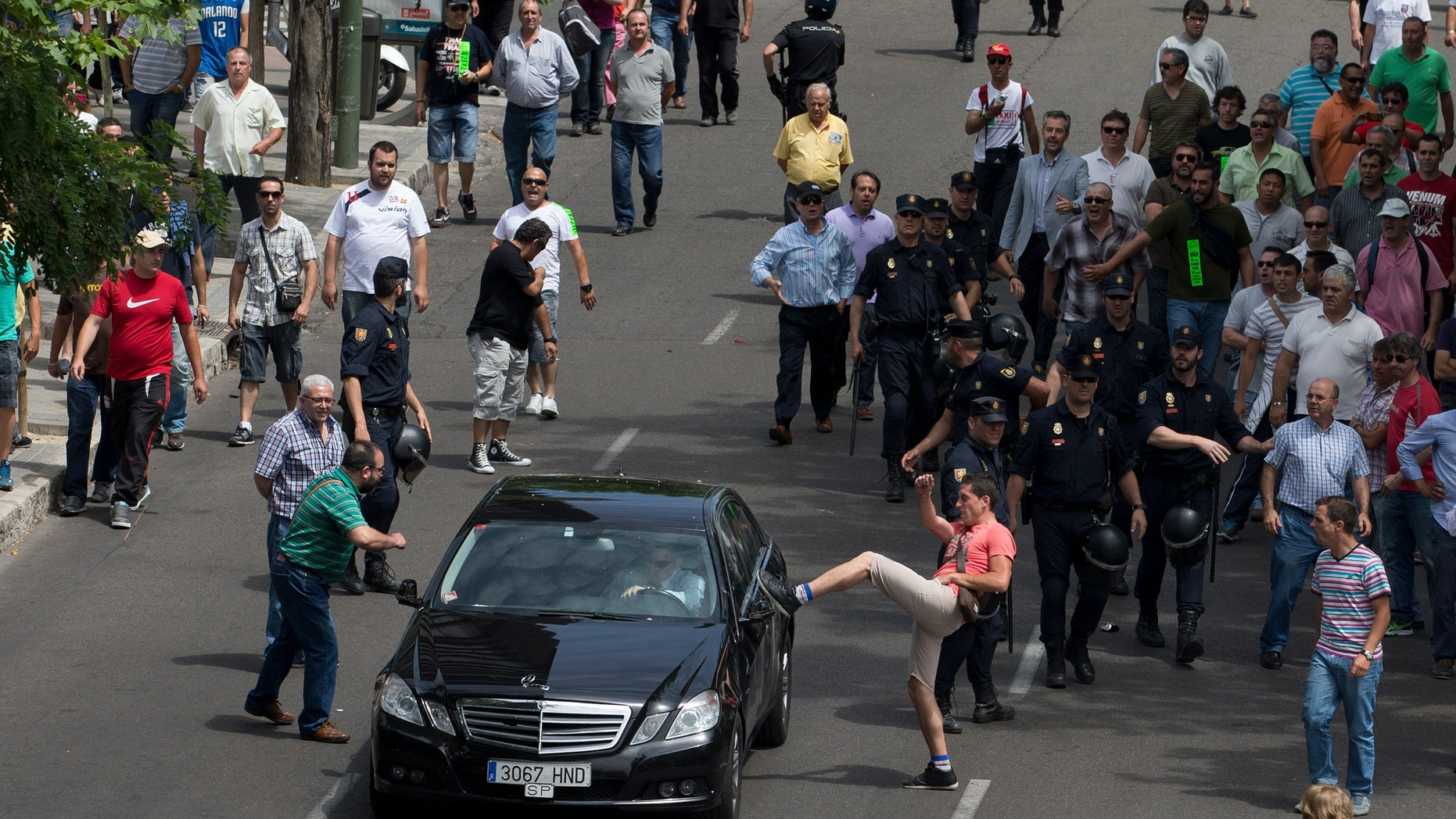 A demonstrator kicks a car during a taxi strike and protest in Madrid, Spain, in June 2014