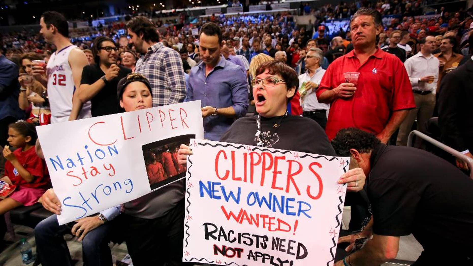 Fans hold up signs in support of the Los Angeles Clippers before Game 5 of an opening-round NBA basketball playoff series between the Clippers and the Golden State Warriors on Tuesday, April 29, 2014, in Los Angeles. NBA Commissioner Adam Silver announced Tuesday that Clippers owner Donald Sterling has been banned for life by the league. (AP Photo/Ringo H.W. Chiu)