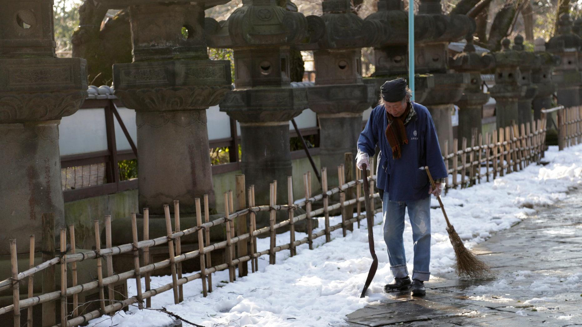 A worker walks away after shoveling snow off a court yard at a temple in Tokyo, Sunday, Feb. 16, 2014. (AP Photo/Shizuo Kambayashi)