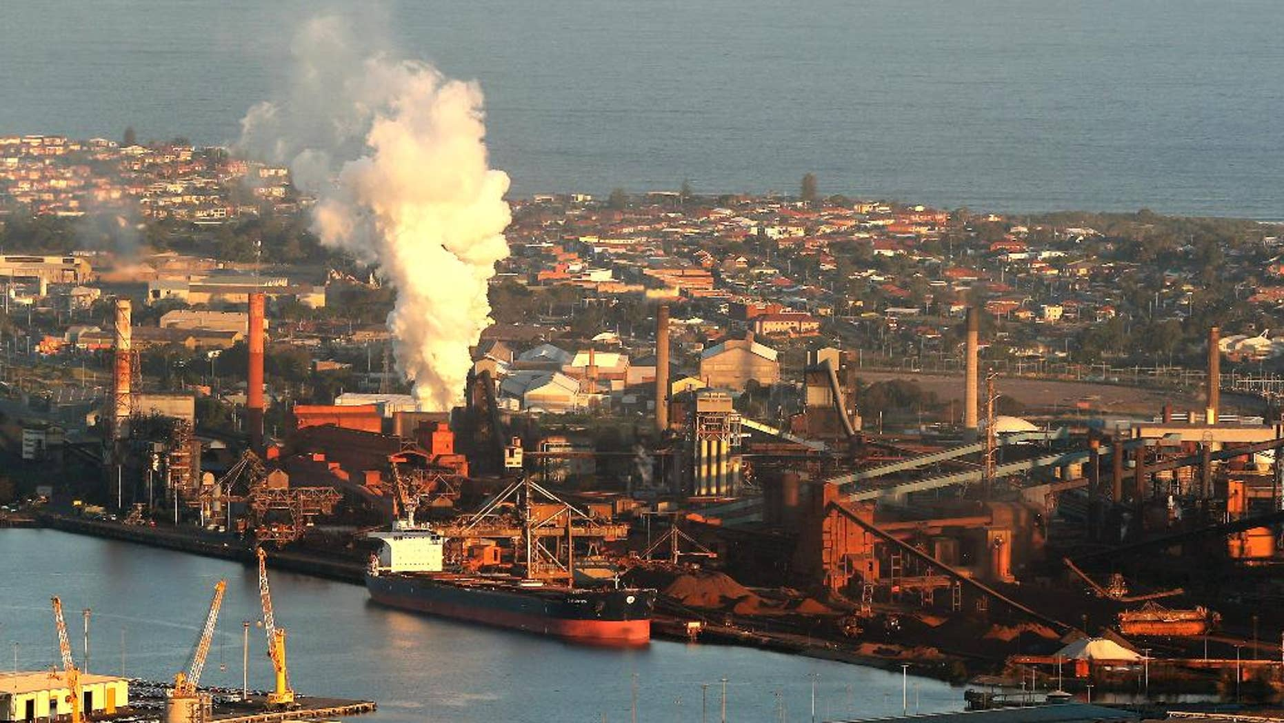 FILE - In this July 2, 2014 file photo, smoke billows out of a chimney stack of BHP steelwork factories at Port Kembla, south of Sydney, Australia. The world's biggest miner, BHP Billiton, on Tuesday, Aug. 16, 2016, reported a $6.4 billion loss, the worst full-year result in the Anglo-Australian company's history. BHP said the result for the fiscal year ending June 30 came from a 31 percent fall in revenue to $30.1 billion amid weak commodity prices, write downs of U.S. oil and gas assets and a disaster at a Brazilian mining joint venture. (AP Photo/Rob Griffith, File)