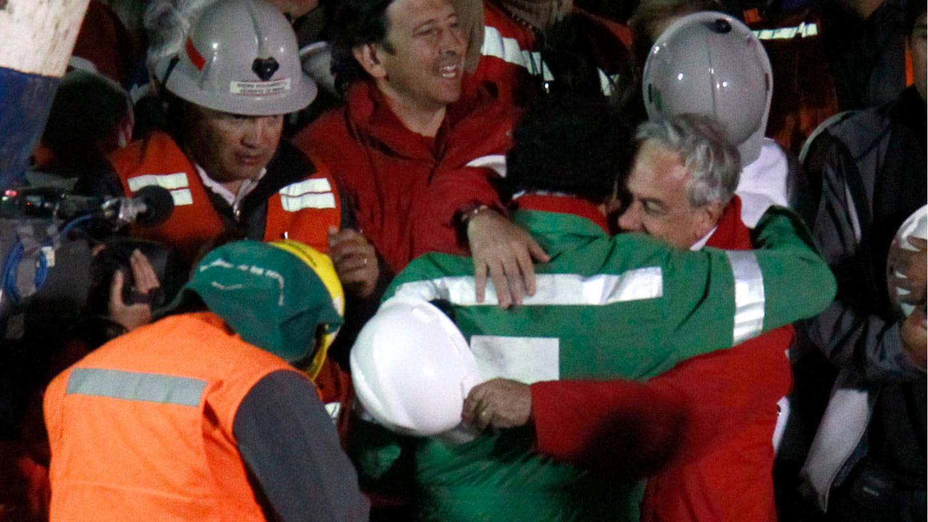 The last rescued miner, Luis Urzua, center wearing green, hugs Chile's President Sebastian Pinera after being rescued from the collapsed San Jose gold and copper mine where he had been trapped with 32 other miners for over two months near Copiapo, Chile, Wednesday Oct. 13, 2010. The 69-day underground ordeal reached its end Wednesday night after 33 trapped miners were hauled up in a cage through a narrow hole drilled through 2,000 feet of rock. (AP Photo/Roberto Candia)