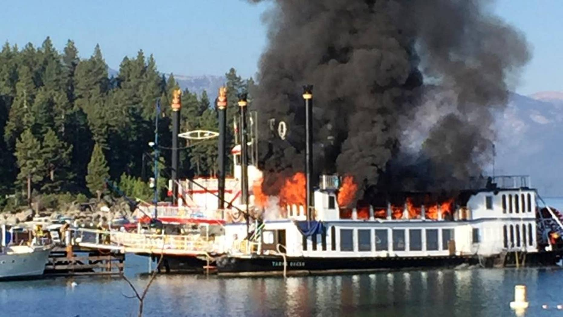 A fire rips through the second deck of a docked tourist cruise boat under repair at Lake Tahoe, in Reno, Nev., Tuesday, Aug. 16, 2016. The fire severely damaged the popular paddle wheeler and injuring two workers on board before crews extinguished the flames that sent a plume of black smoke high above the Sierra waters. (Zach Hastie via AP)