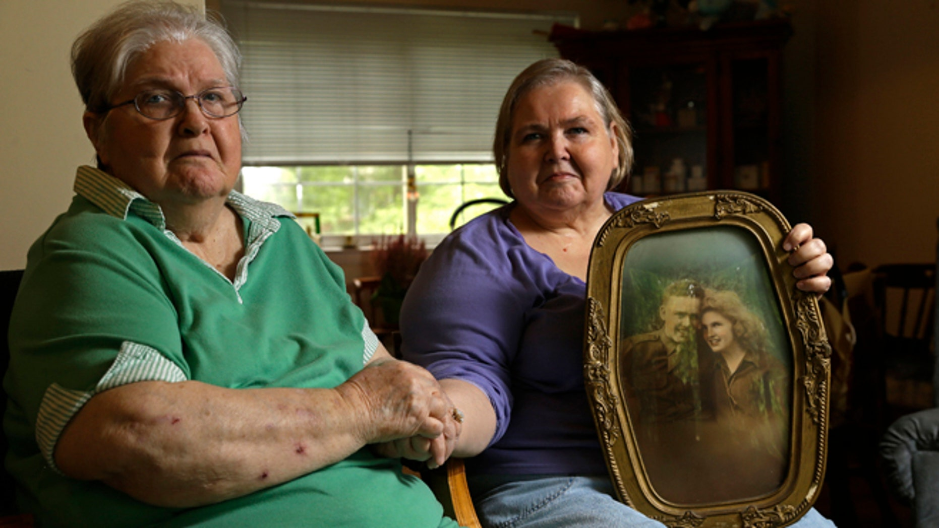 In this photo taken Monday, July 1, 2013 in Chapel Hill, N.C., Shelia Reese, right, sits with her mother Chris Tench holding a portrait of Tench and her father Kenneth F. Reese, a soldier who is still Missing In Action from the Korean War. Tench, who was later remarried, has never known what happened to her husband.
