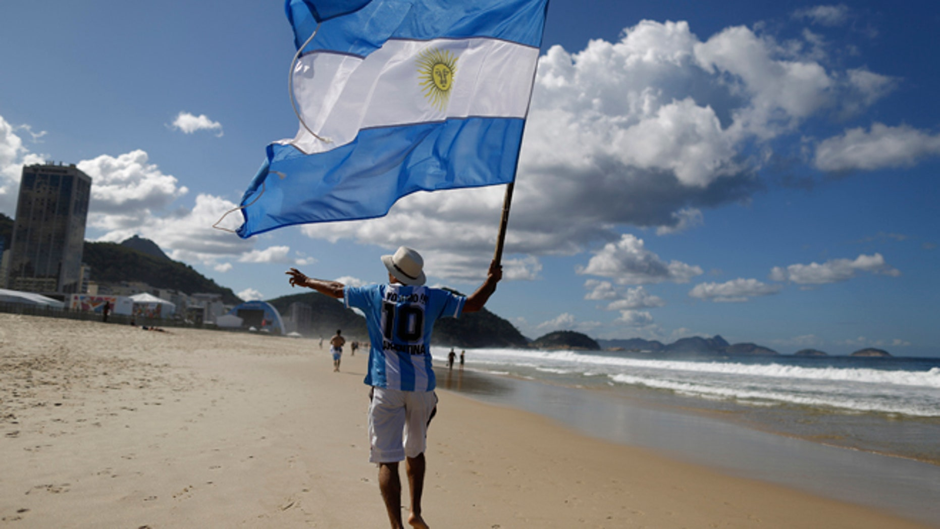 FILE - In this  July 14, 2014, file photo, an Argentina soccer fan waves Argentina's national flag the morning after his team was defeated by Germany at the World Cup final, on Copacabana beach in Rio de Janeiro, Brazil. Local media reports say tens of thousands of Argentine fans have remained in the country after the tournament ended. But the prospect of a large number of foreigners selling handicrafts, juggling at intersections for handouts or relying on government social services for poor Brazilians has officials worried. (AP Photo/Leo Correa, File)
