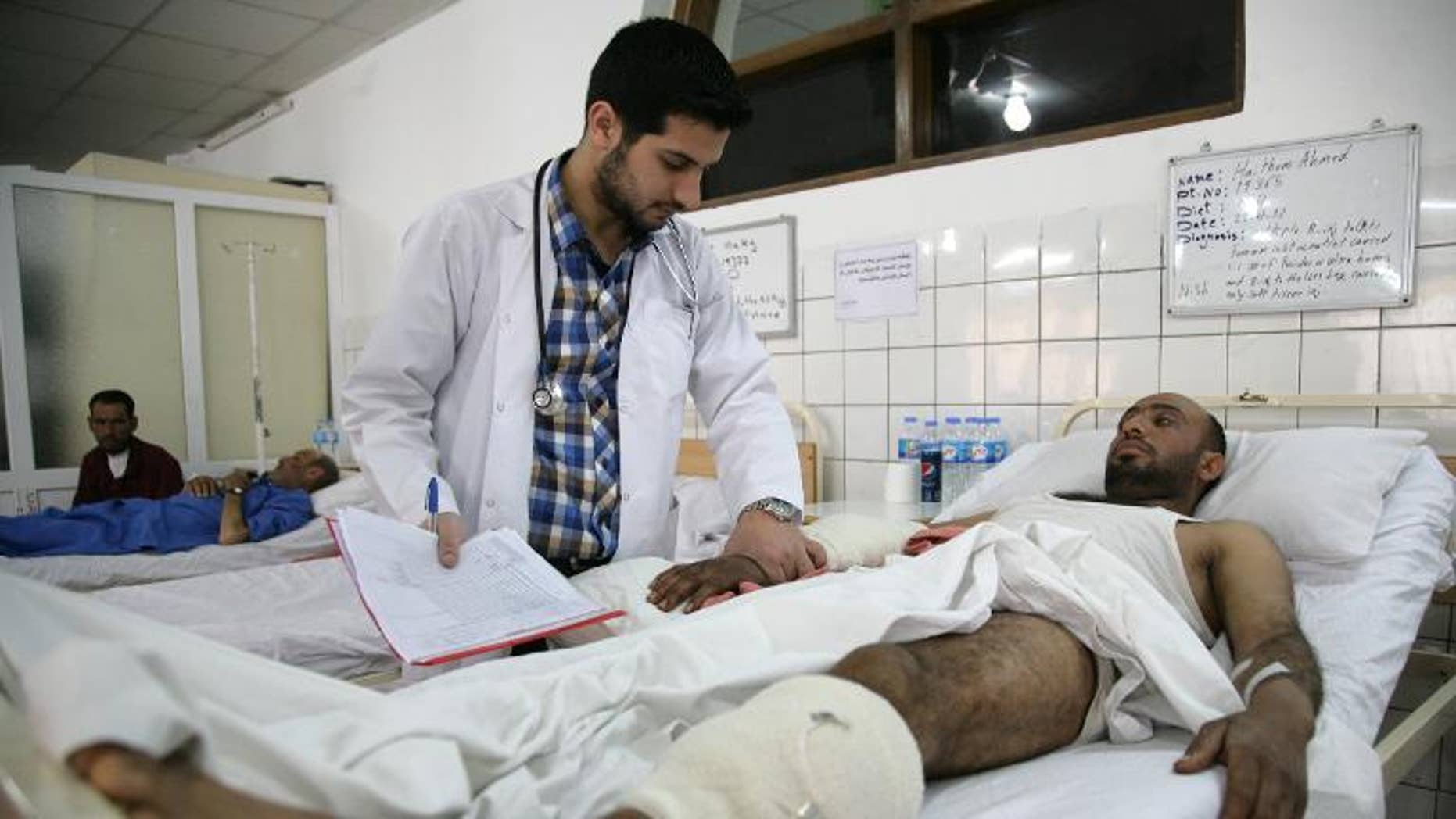 A doctor checks on a wounded man in hospital in Arbil on April 25, 2013