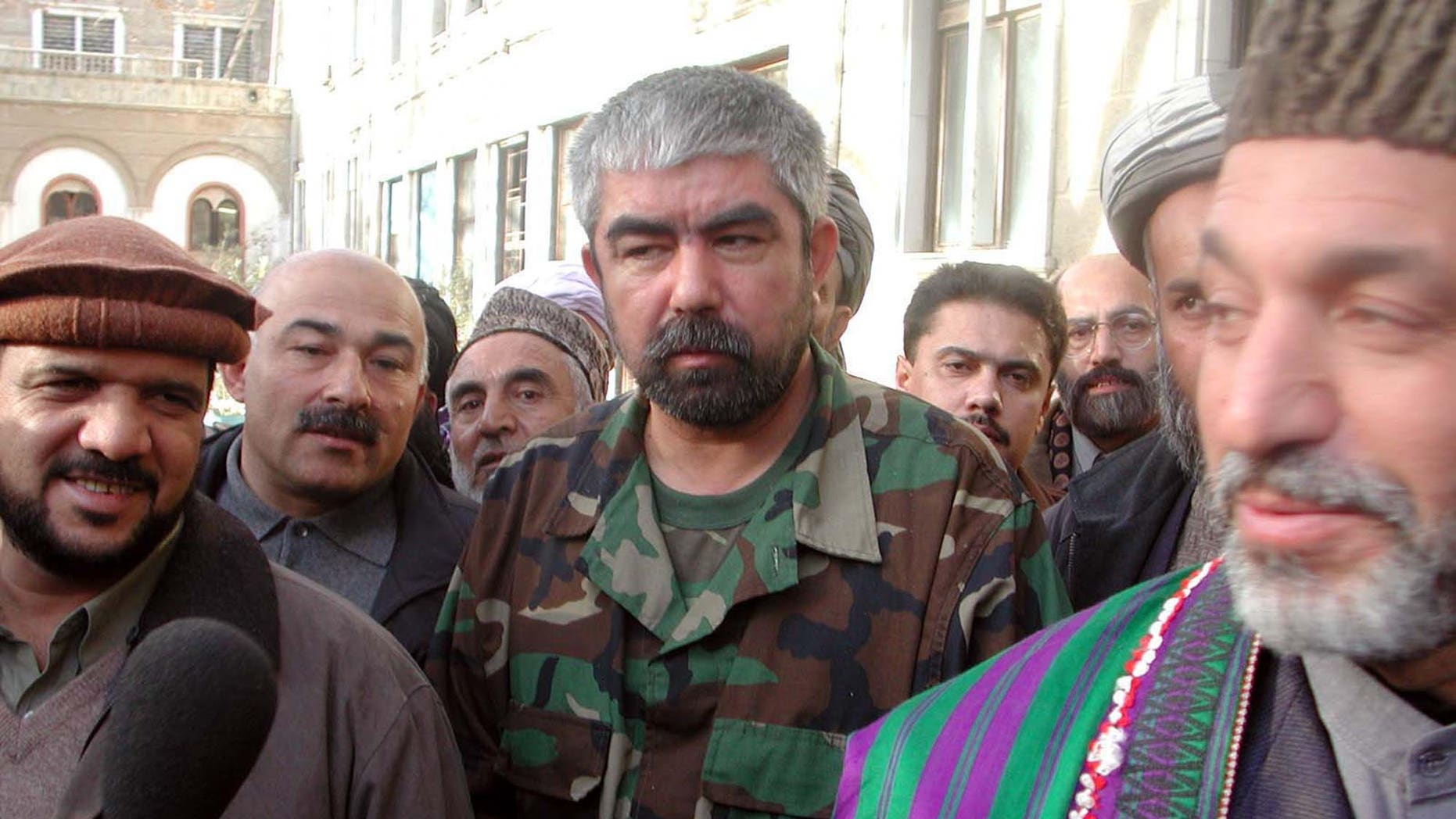 In this Monday, Dec. 24, 2001 file photo, Afghanistan's new premier Hamid Karzai, right, stands with Uzbek General Abdul Rashid Dostum, center, with Mohammed Qasim Fahim, left, as defense ministers.
