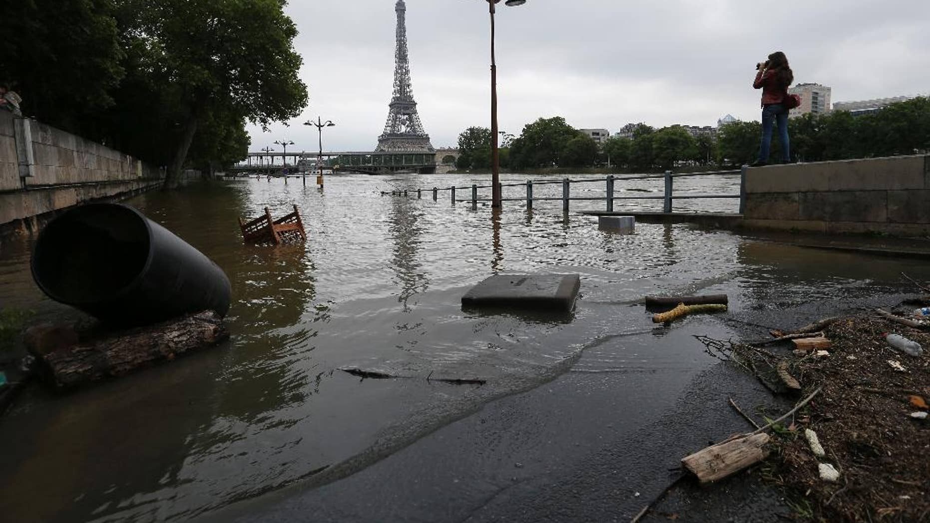 A woman takes photos of the flooded banks of the Seine river in Paris, France Saturday June 4, 2016. The level of the Seine started to drop after peaking earlier in the morning. Both the Louvre and Orsay museums were closed as officials said the Seine had been at its highest level in nearly 35 years. (AP Photo/Francois Mori)