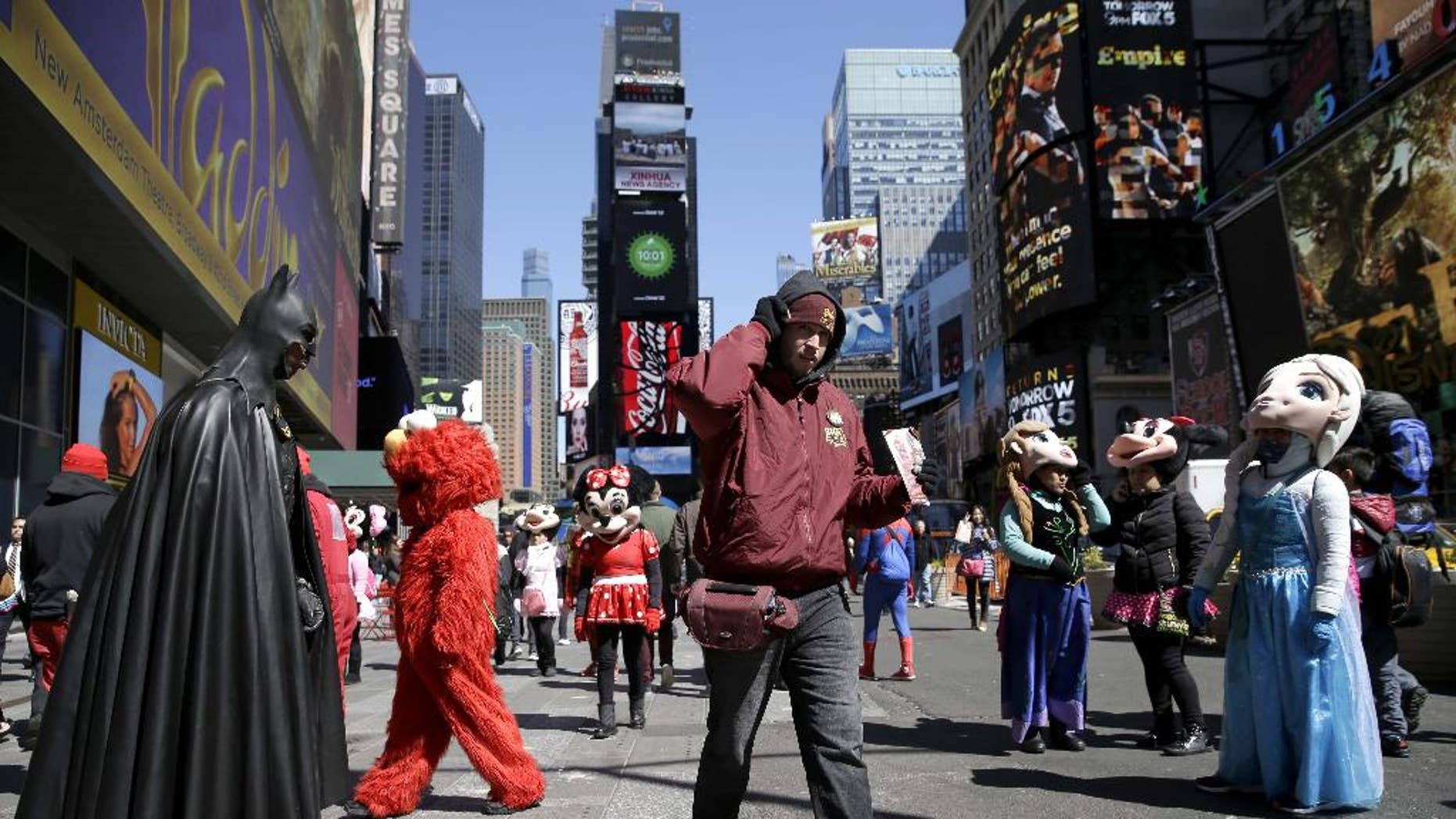 FILE - In this March 29, 2016 file photo, a bus tour ticket seller, center, walks through a group of costumed characters in Times Square in New York. New York City workers have started painting teal rectangles in pedestrian plazas designating where costumed characters can pose with tourists in Times Square. Starting June 21, street performers and costumed characters will be restricted to those areas when soliciting tips from tourists.  (AP Photo/Seth Wenig)