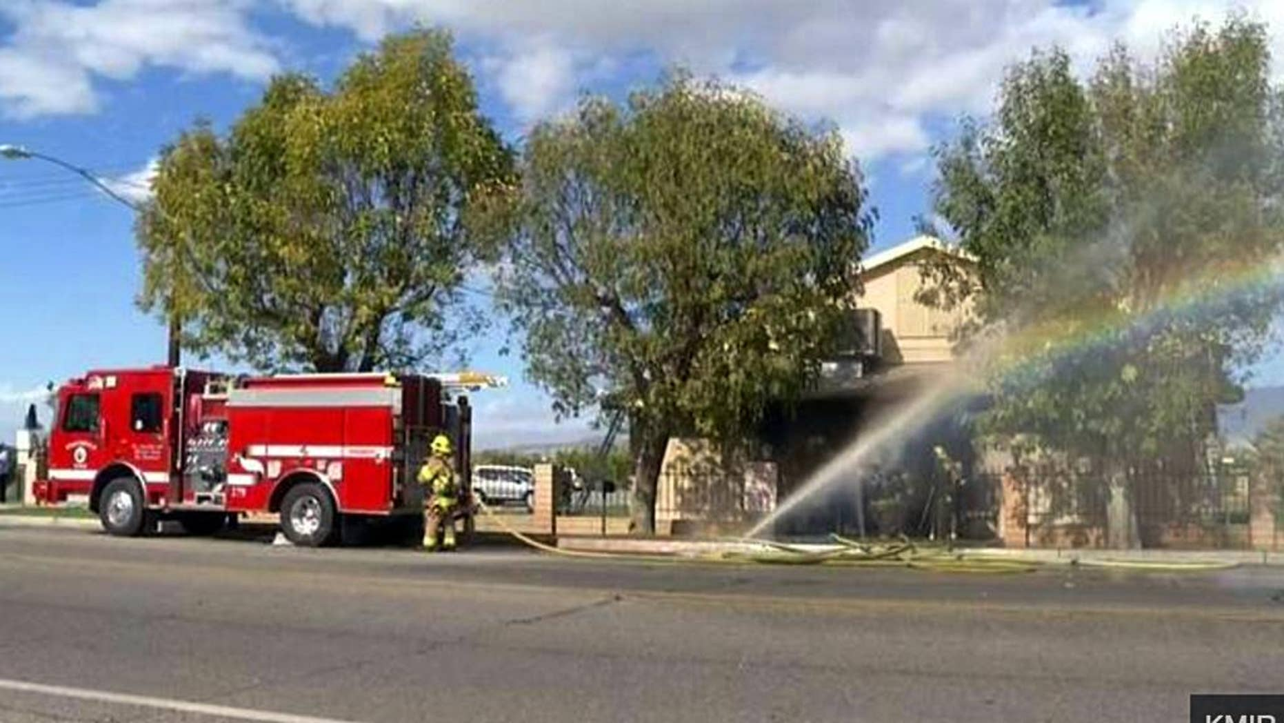 In this image made from video provided by KMIR-TV, firefighters battle flames at the Islamic Center of Palm Springs, a mosque in Coachella, Calif., just east of Palm Springs, early Friday, Dec. 11, 2015. The fire was contained to the small building's front lobby, and no one was injured. Its cause is under investigation. (KMIR-TV via AP) TV OUT. MANDATORY CREDIT