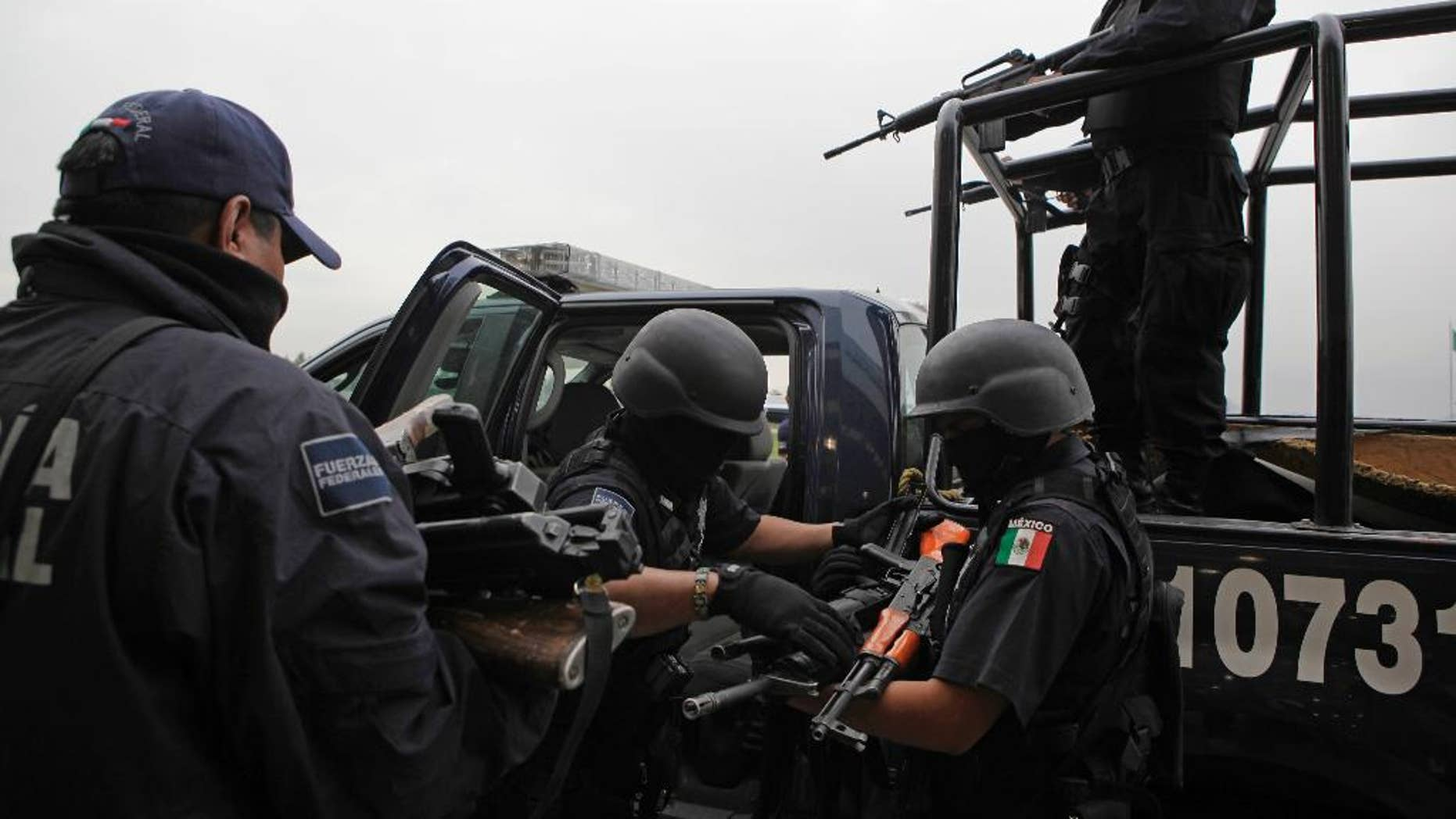 FILE - In this June 26, 2009 file photo, seized weapons from alleged members of the Beltran Leyva drug cartel are taken away by federal agents after a press conference in Mexico City. In a major embarrassment for Mexican law enforcement, U.S. prosecutors said in documents made public Wednesday, April 6, 2017, that Ivan Reyes Arzate, the commander of the Mexican police's intelligence-sharing unit, was passing information to the Beltran Leyva drug cartel in exchange for cash. (AP Photo/Alexandre Meneghini, File)